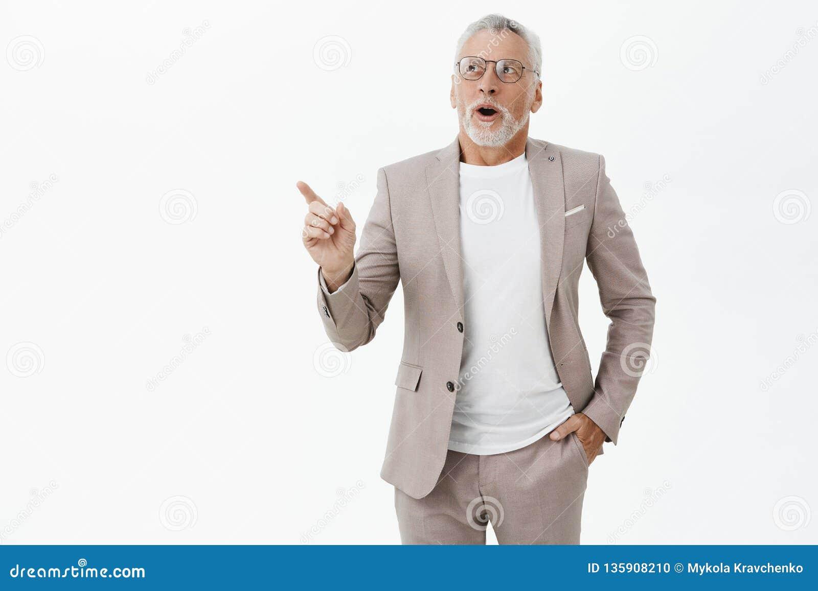 Mannen undrar hur snabba världsändringar Imponerad och förtjust charmig gammal manlig modell med det gråa skägg- och hårinnehavet