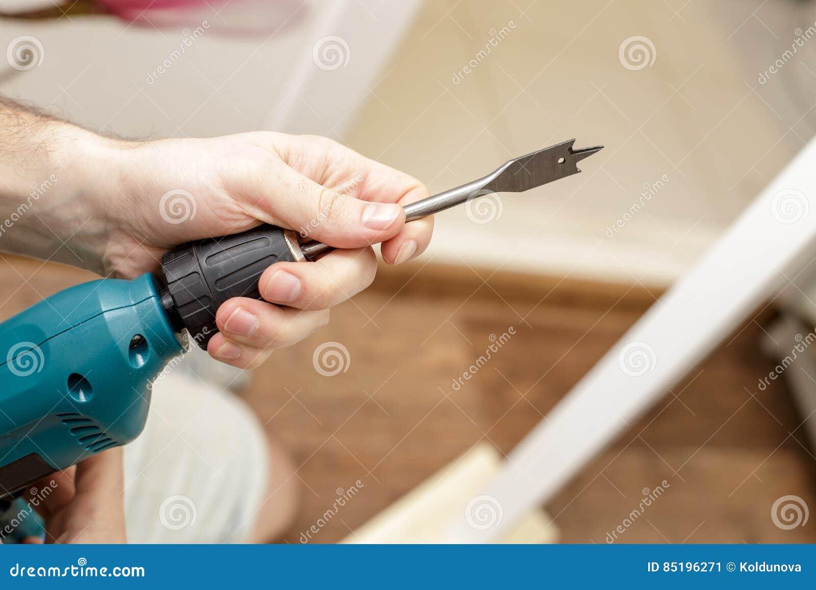 Mannen upprättar biten i drillborren