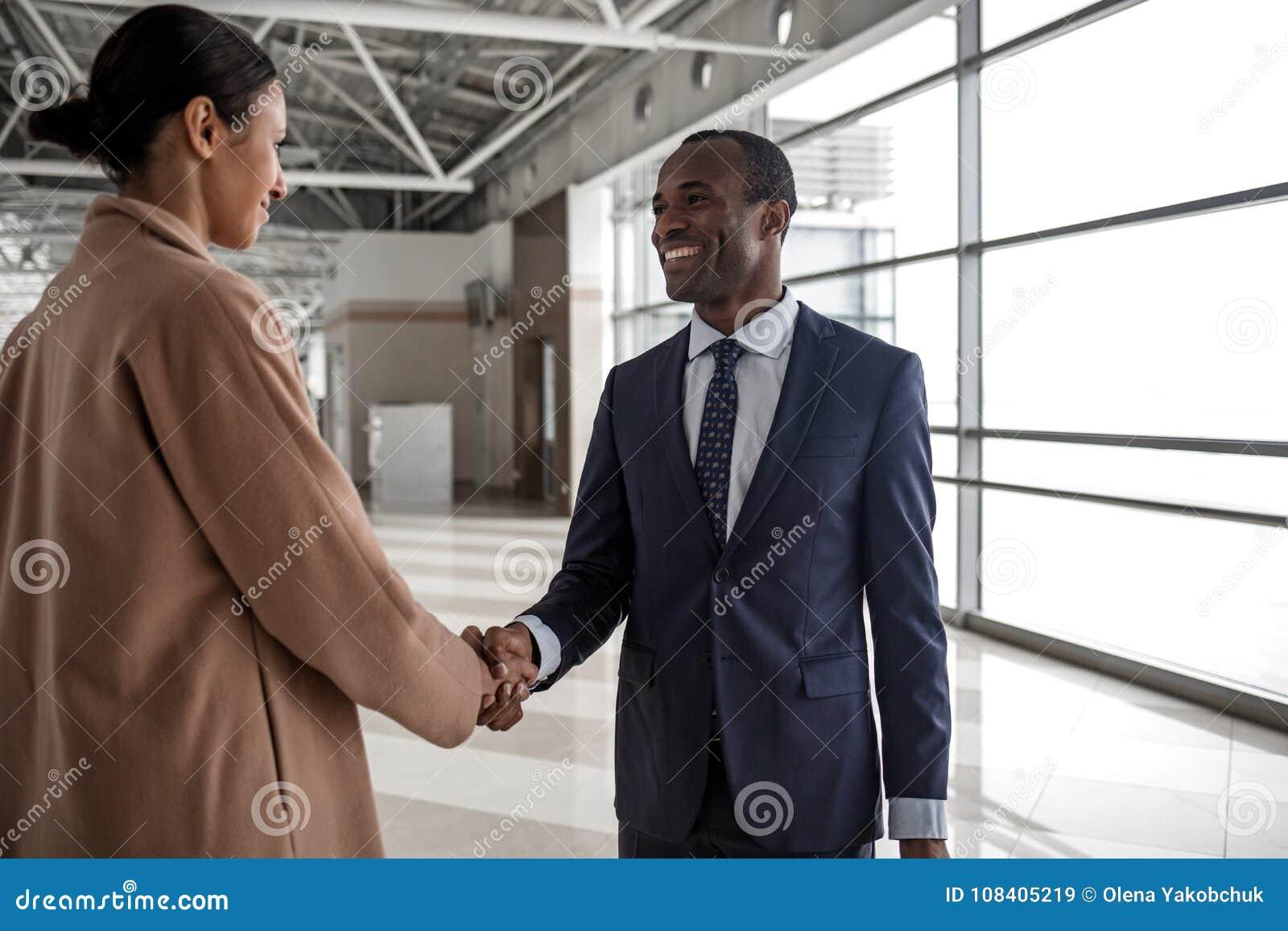 Mannen utbyter hälsningar med den positiva kvinnlign