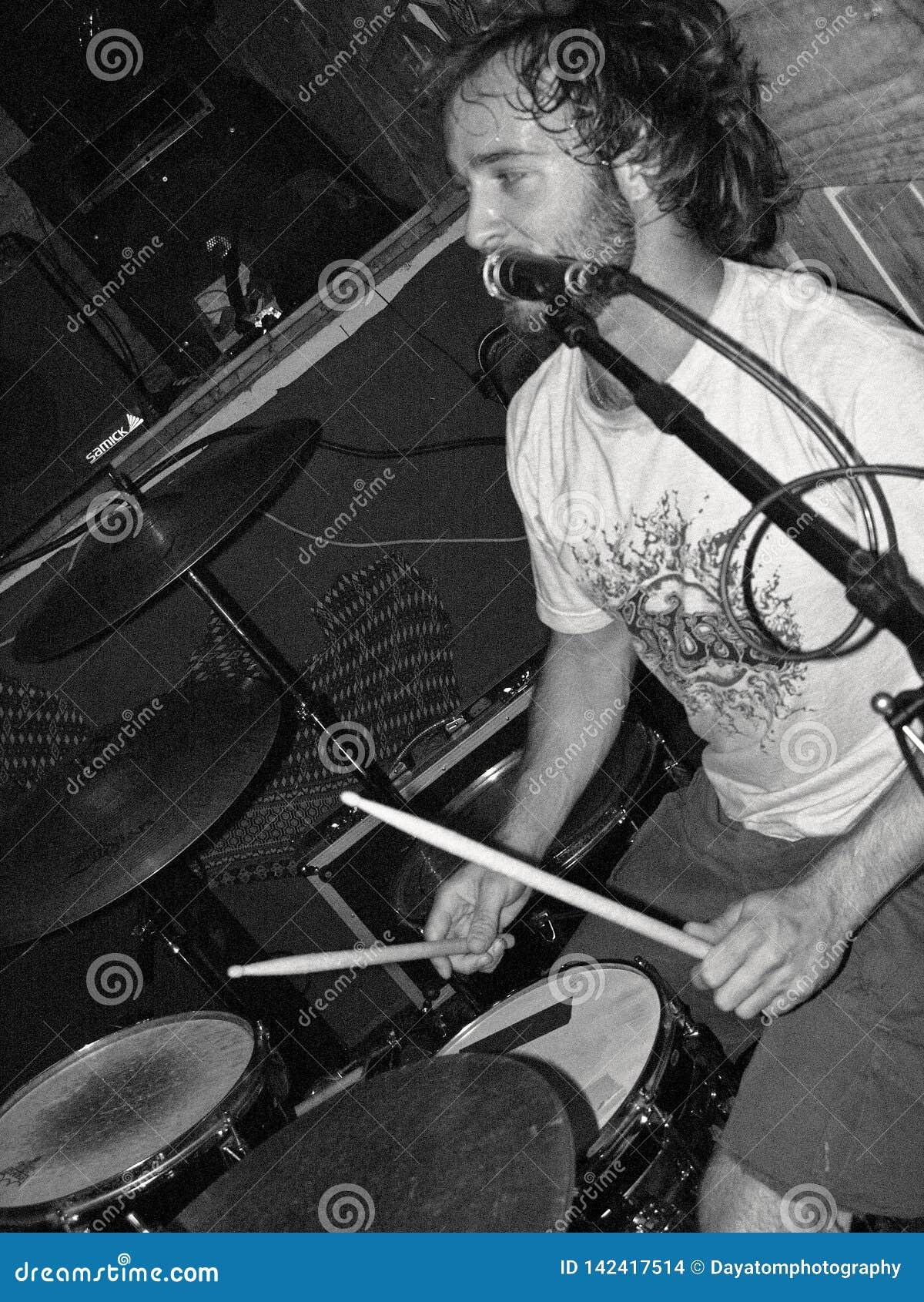 Mannen vaggar vokalisthandelsresanden som nästan sjunger en mikrofonställning som spelar valsarna i svartvitt