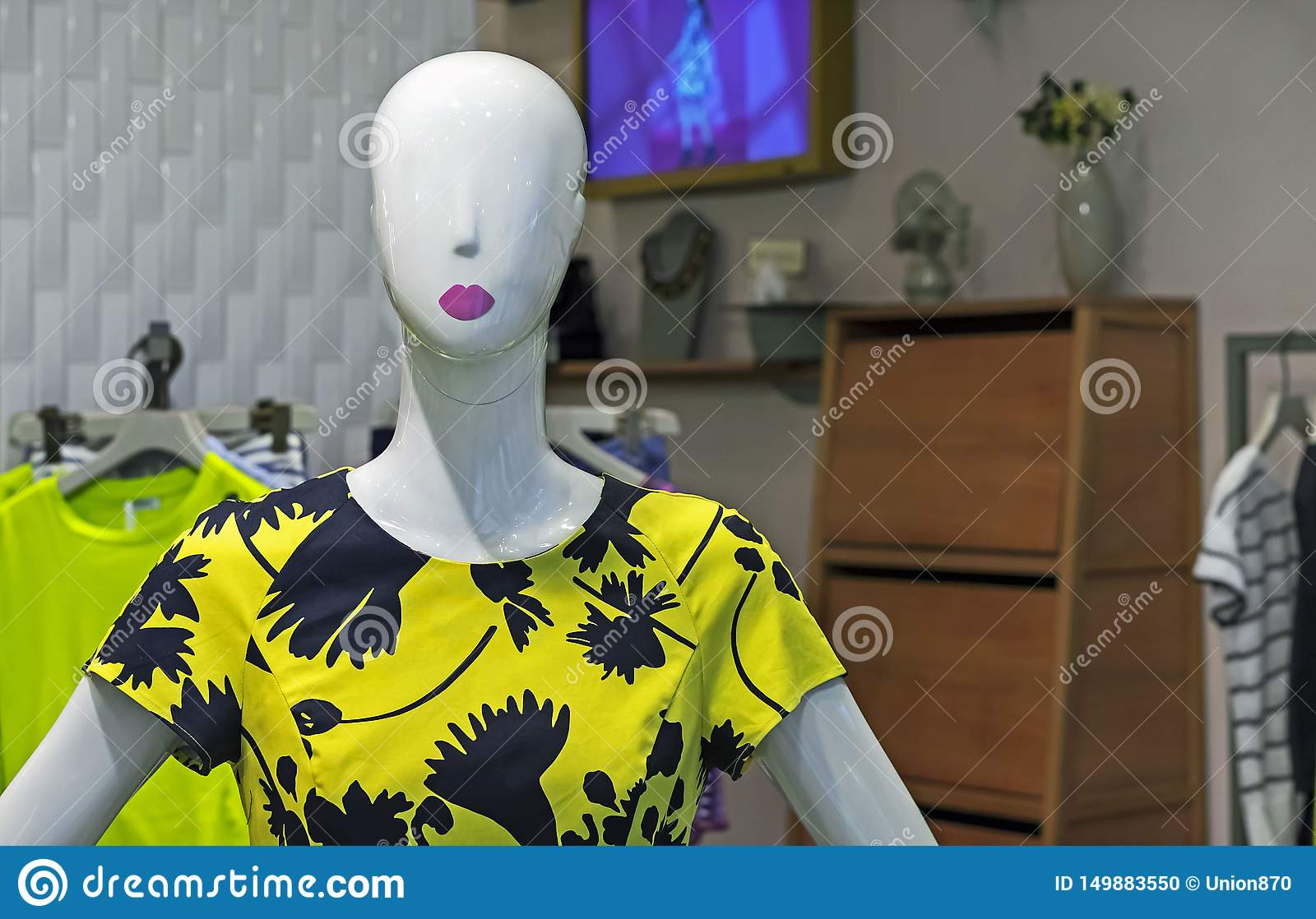 Mannequin female in a yellow dress. Female dummy with summer clothes in a show-window of shop