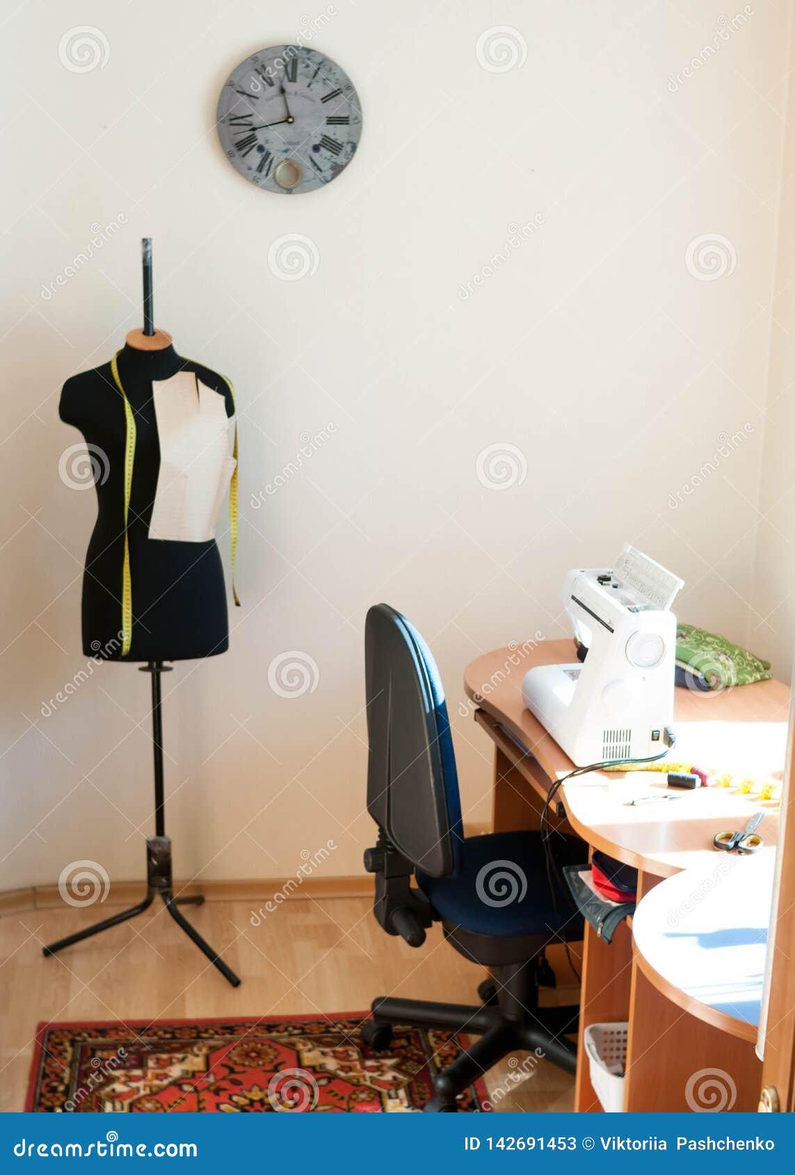 Mannequin i drewniany stół z szwalną maszyną