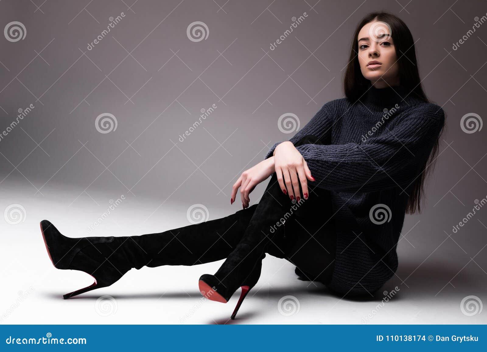 Mannequinvrouw die in die moderne kleren op de vloer zitten op witte achtergrond wordt geïsoleerd