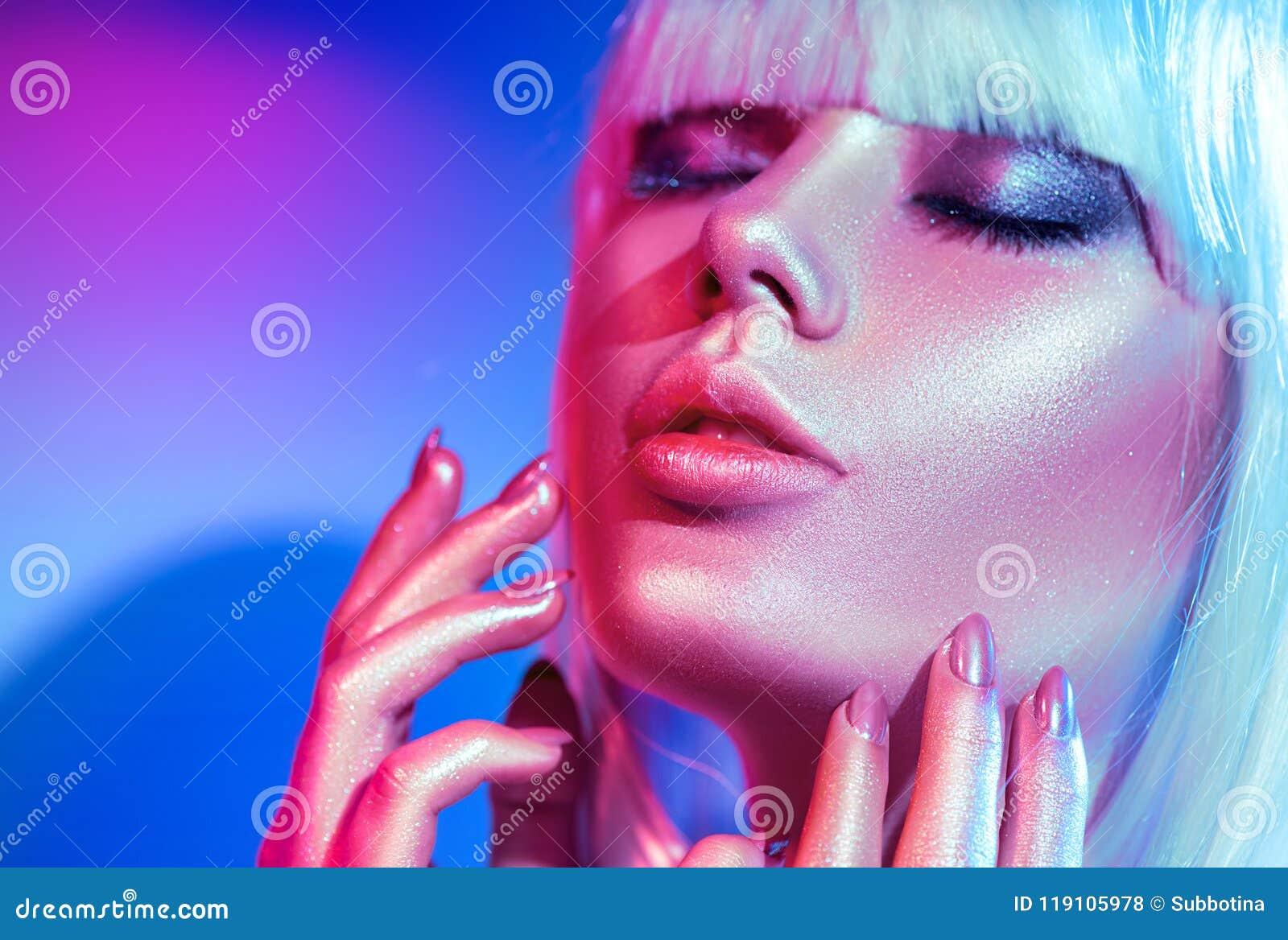 Mannequinvrouw in kleurrijke heldere fonkelingen en neonlichten die in studio stellen
