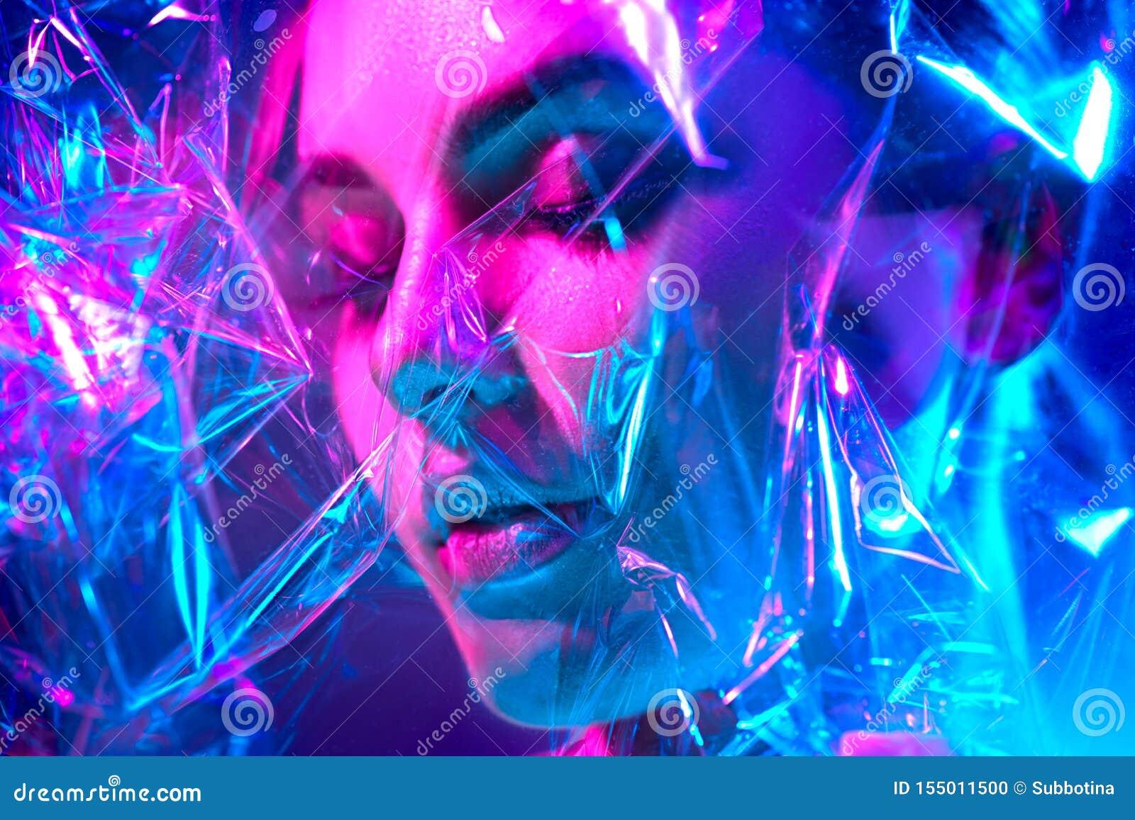 Mannequinvrouw in kleurrijke heldere neonlichten die in studio door transparante film stellen Portret van mooi sexy meisje