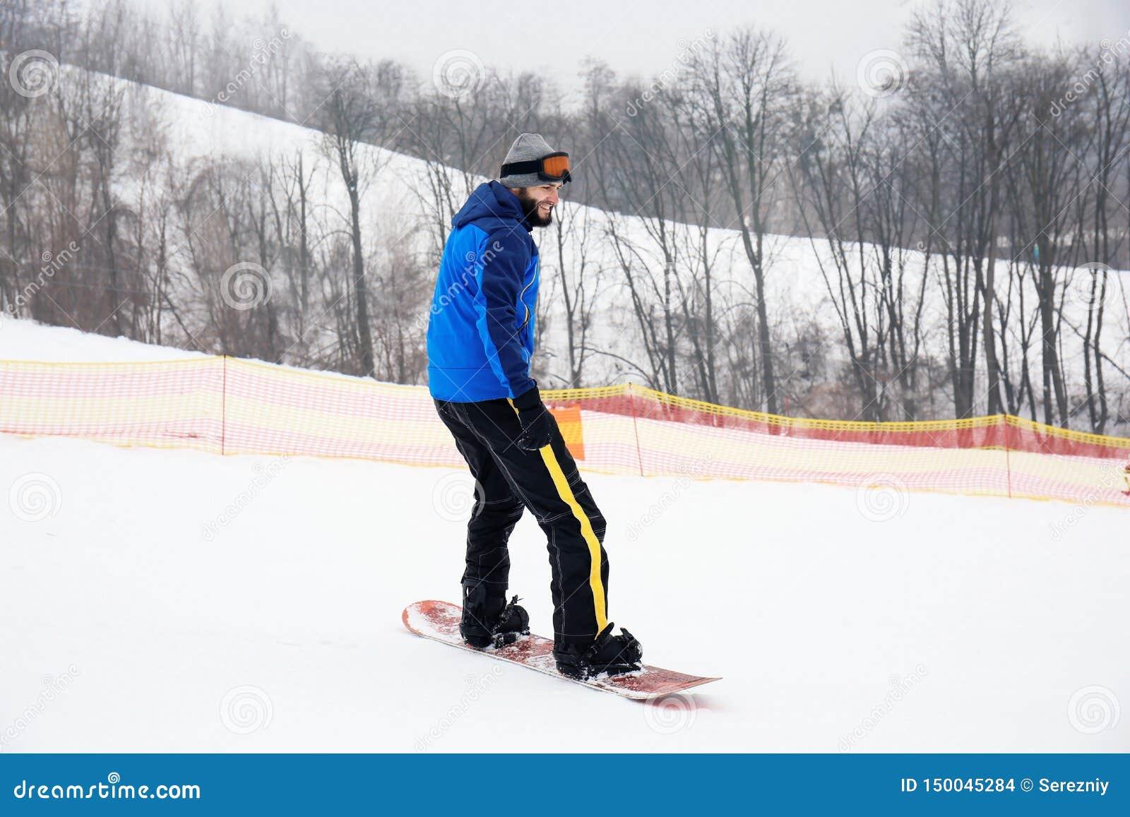 Mannetje snowboarder op helling bij de wintertoevlucht