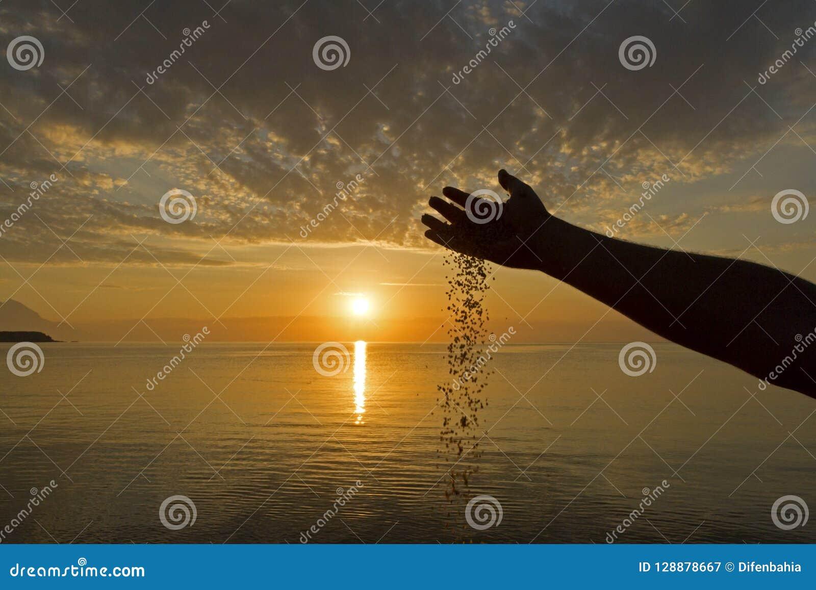 Mannhand gießen Sand auf dem Sonnenaufganghintergrund