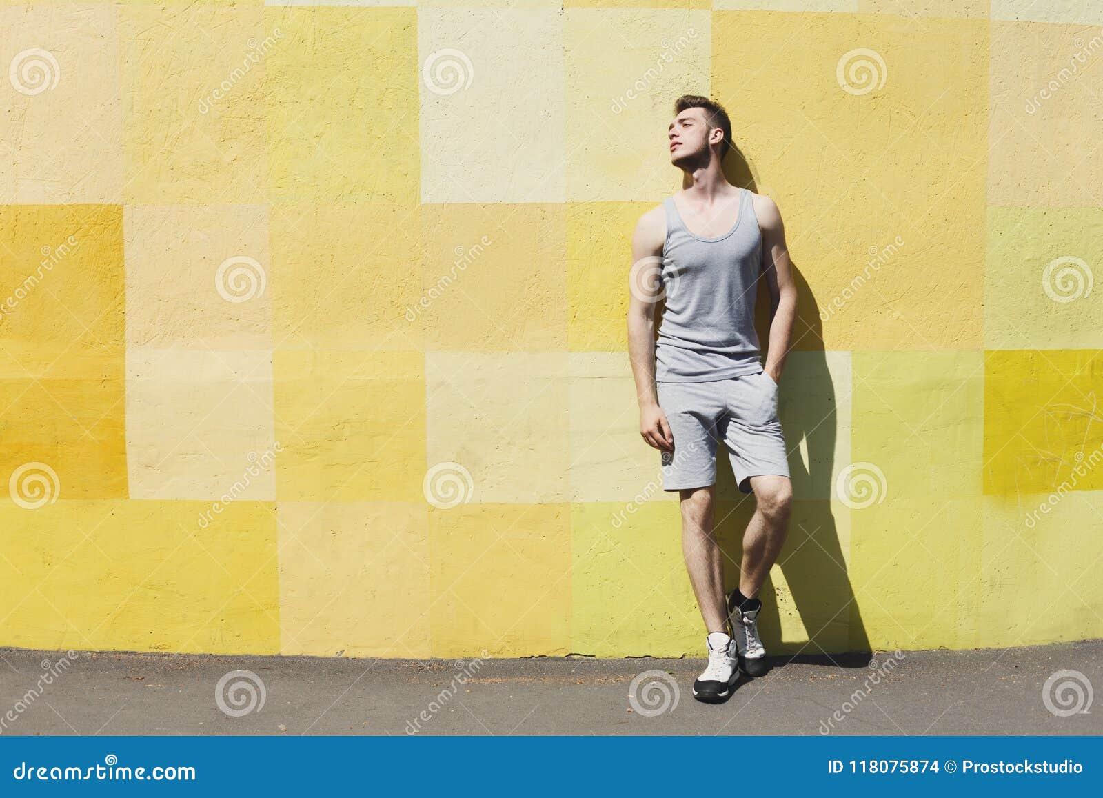Mannläufer hat den Bruch und lehnt sich an der gelben Wand