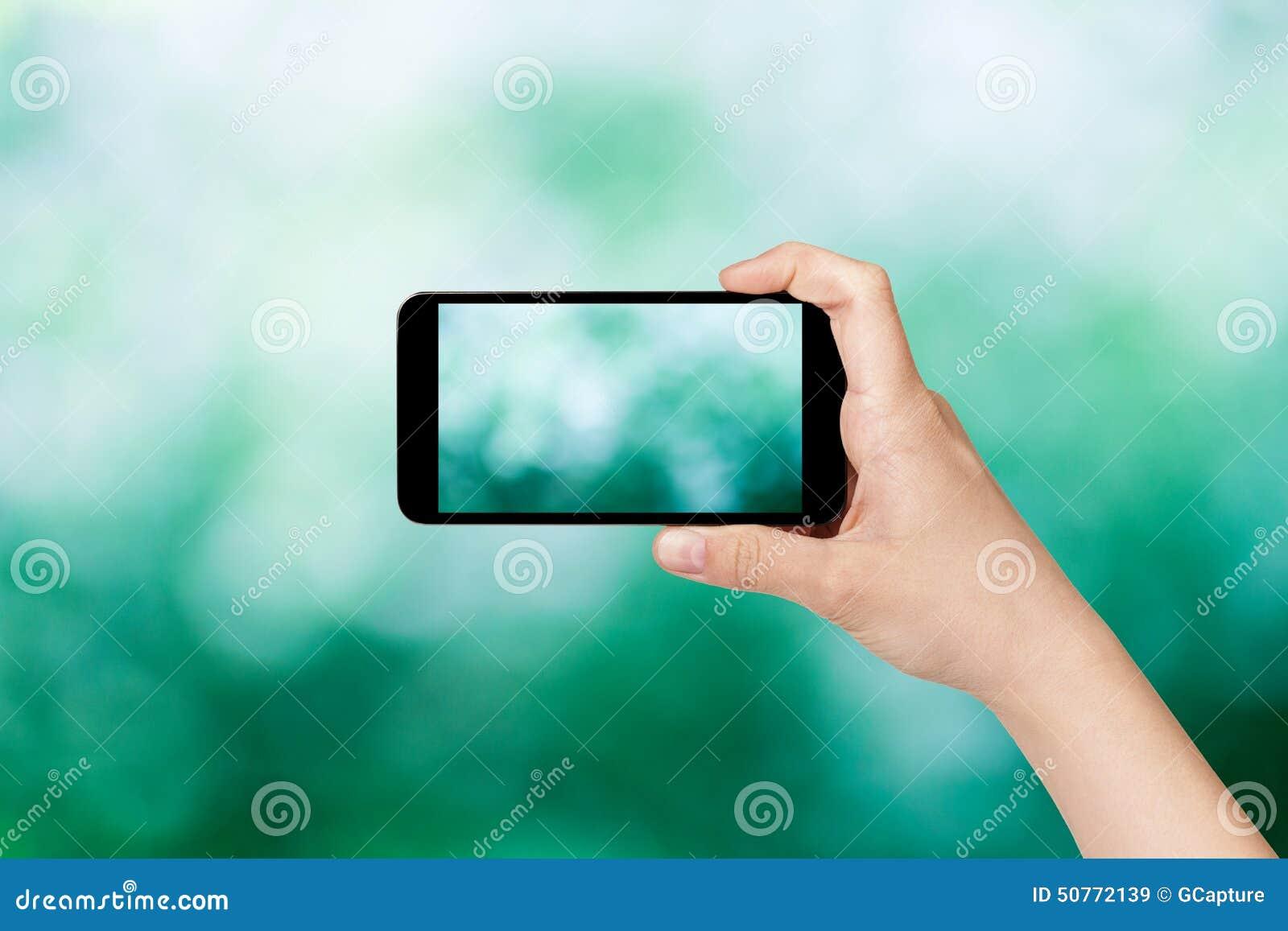 Mano adolescente femenina que toma la imagen con el teléfono elegante