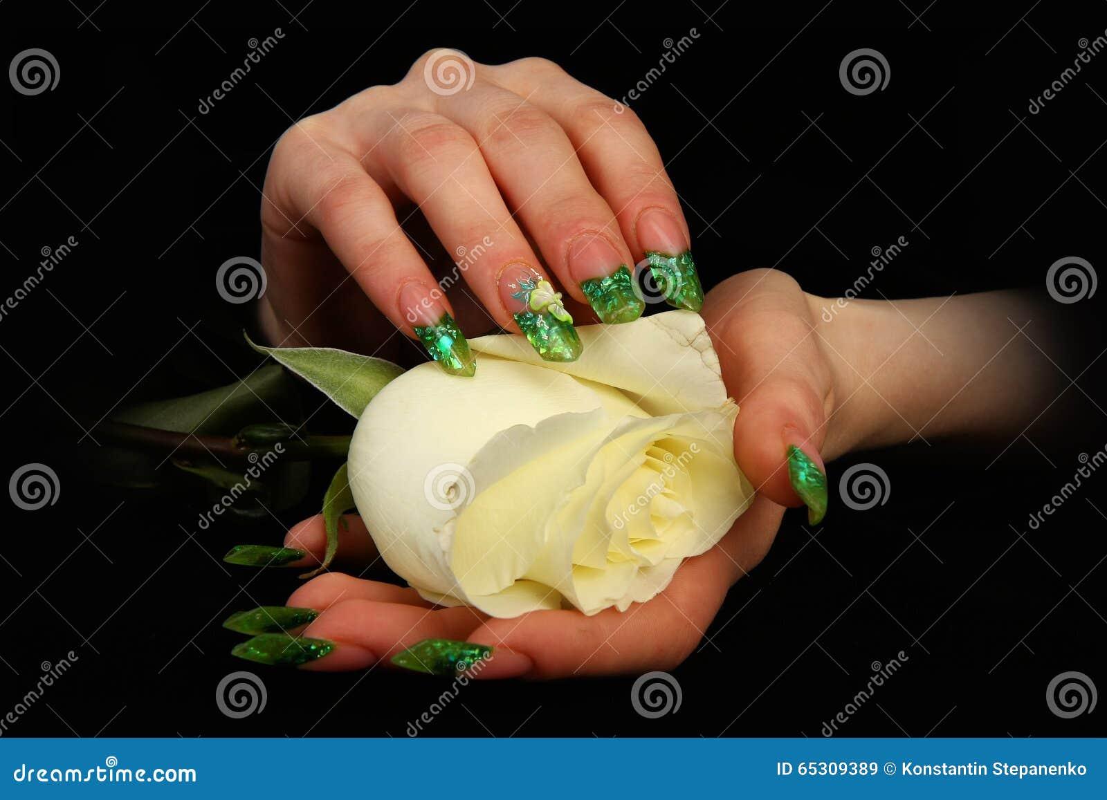 Mano bonita de la mujer con los clavos pintados perfectos en fondo negro