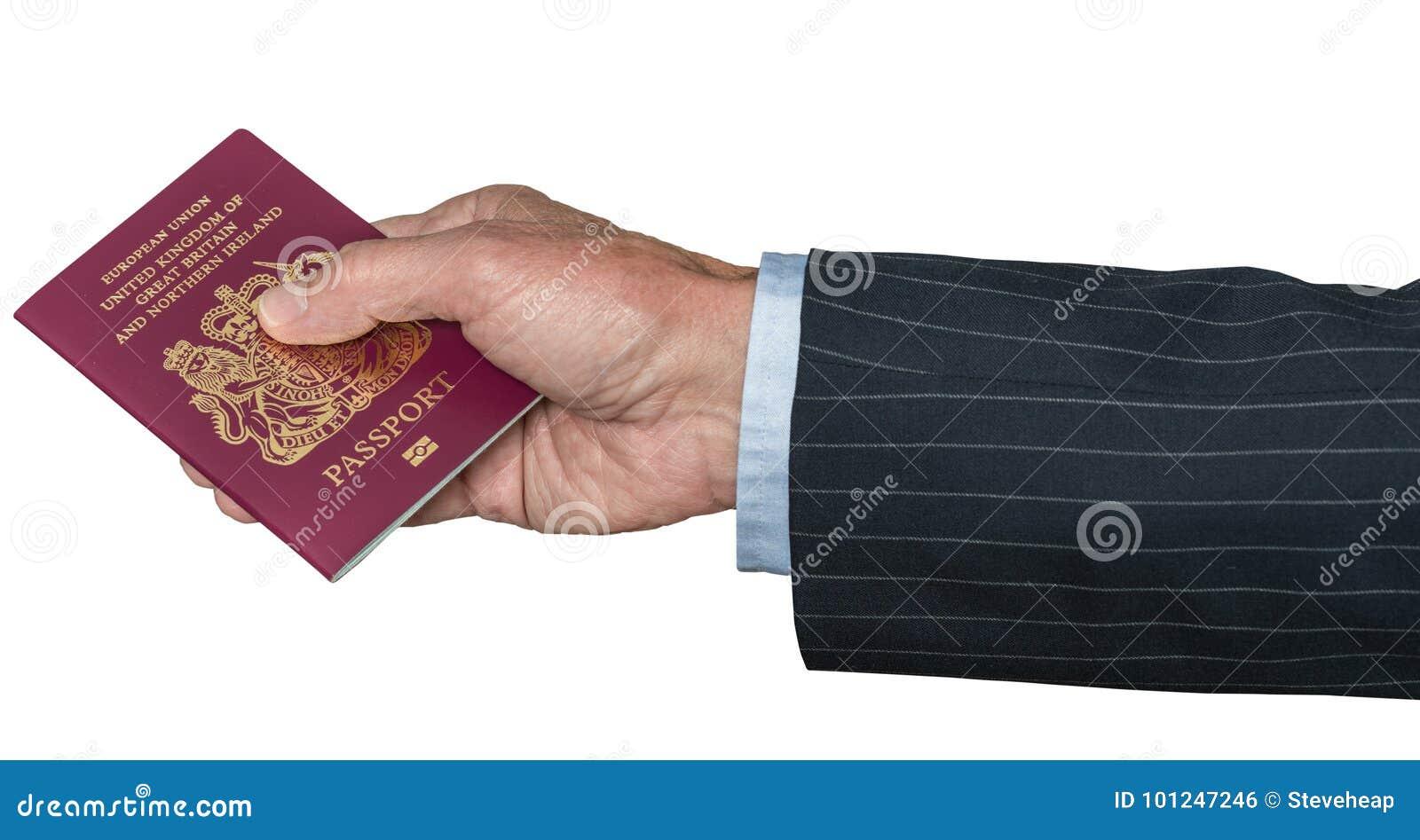 Mano caucásica mayor que sostiene el pasaporte BRITÁNICO