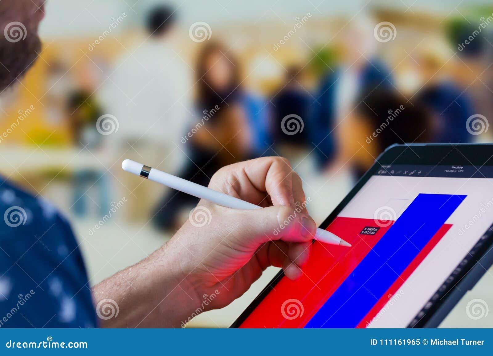 Mano caucásica surgida del cierre usando un iPad para hacer diseño gráfico en un app