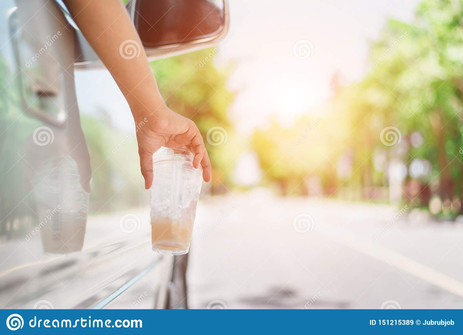 Mano che getta bottiglia di plastica sulla strada