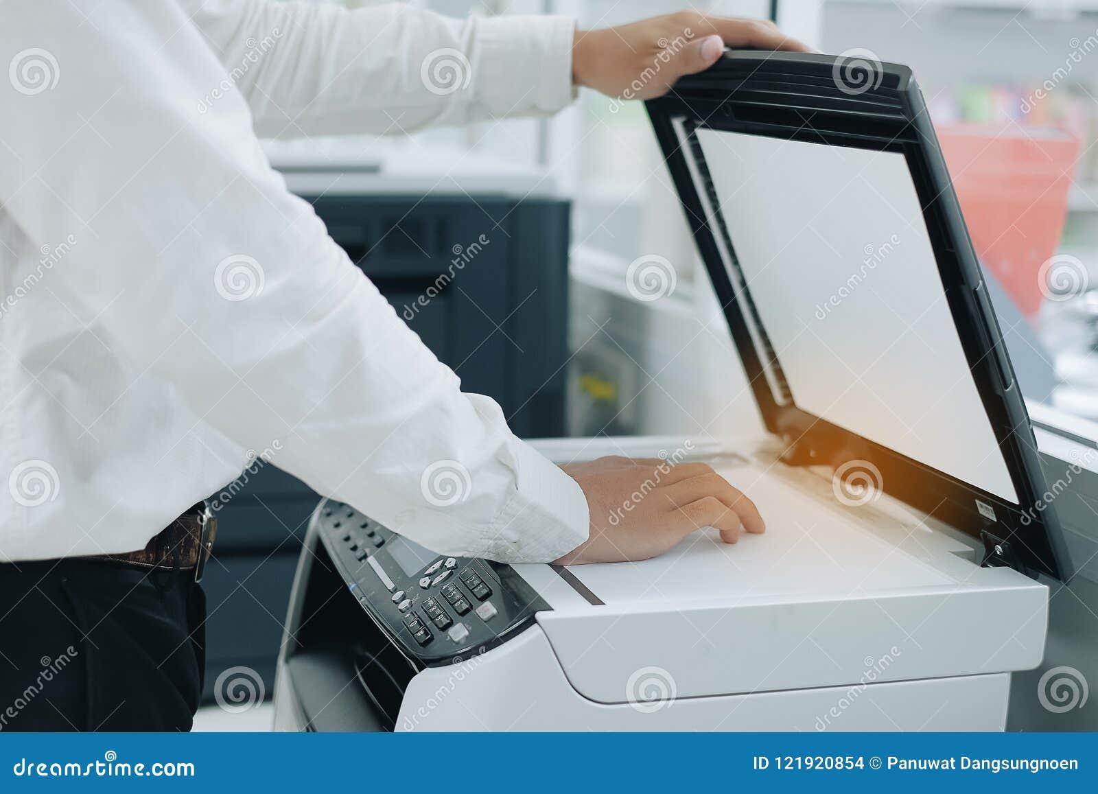 Mano che mette una carta del documento nell analizzatore di stampante o nella macchina della copia laser in ufficio
