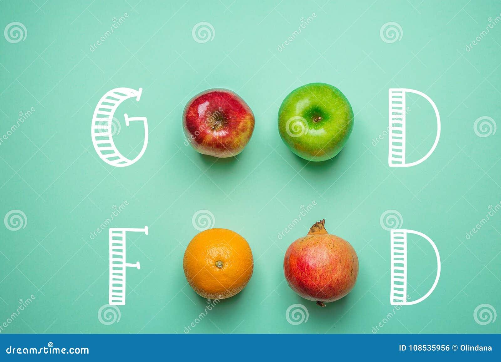Mano che segna buon alimento con lettere sul fondo del turchese con il melograno rosso verde arancio delle mele di frutti Vegano