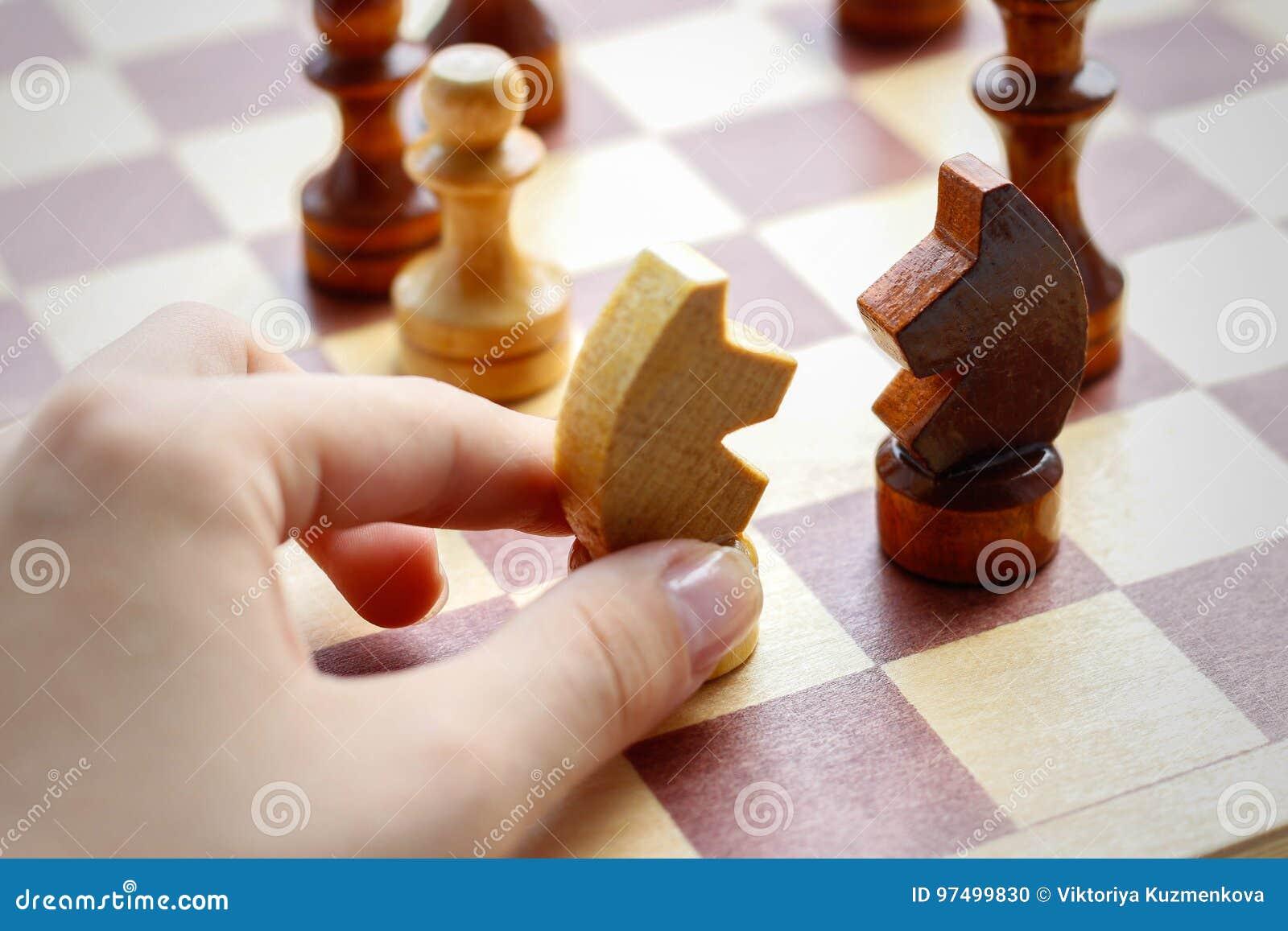 Mano che tiene l insieme di scacchi di legno sulla scacchiera Scacchi Il nero e W