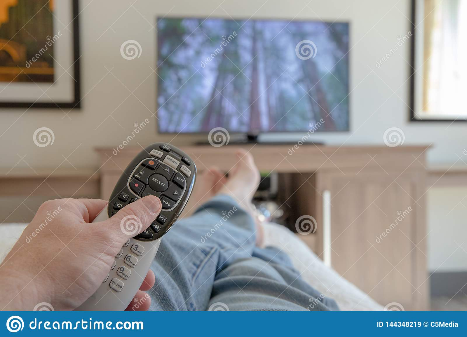 Mano che tiene telecomando per la TV mentre rilassandosi con i piedi propped - su profondità di campo bassa