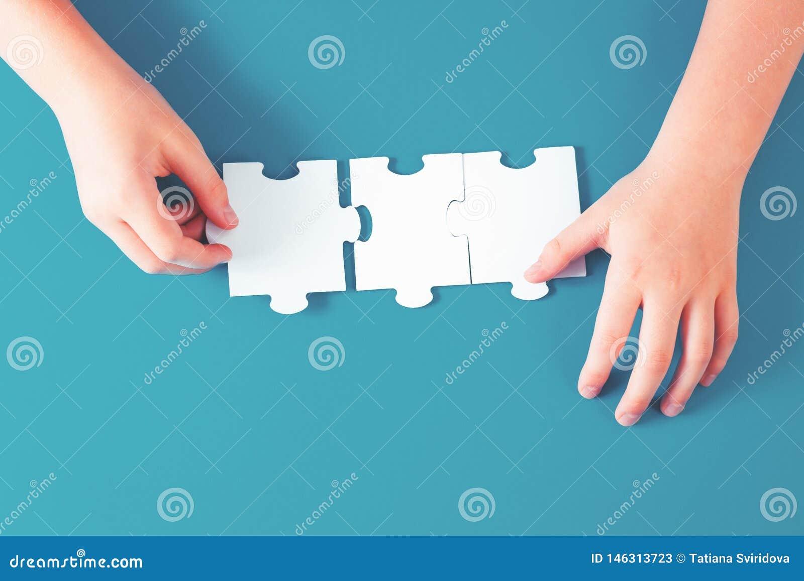Mano che tiene un pezzo del puzzle