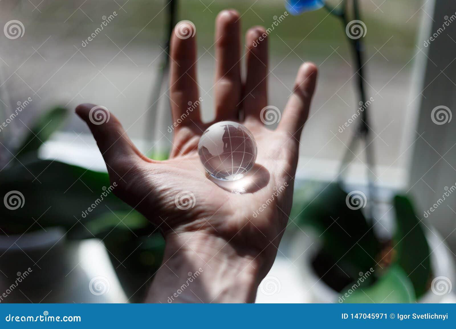 Mano che tiene un piccolo globo di cristallo concetto di corsa