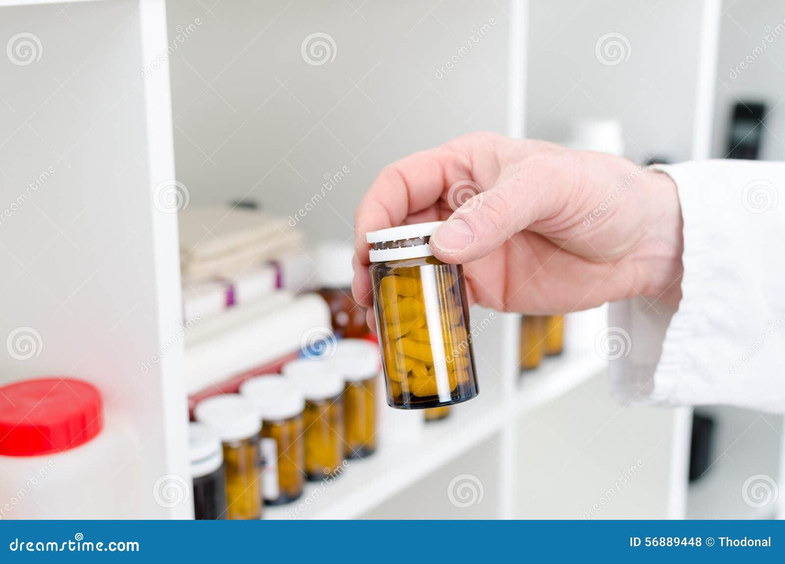 Mano che tiene una bottiglia delle pillole