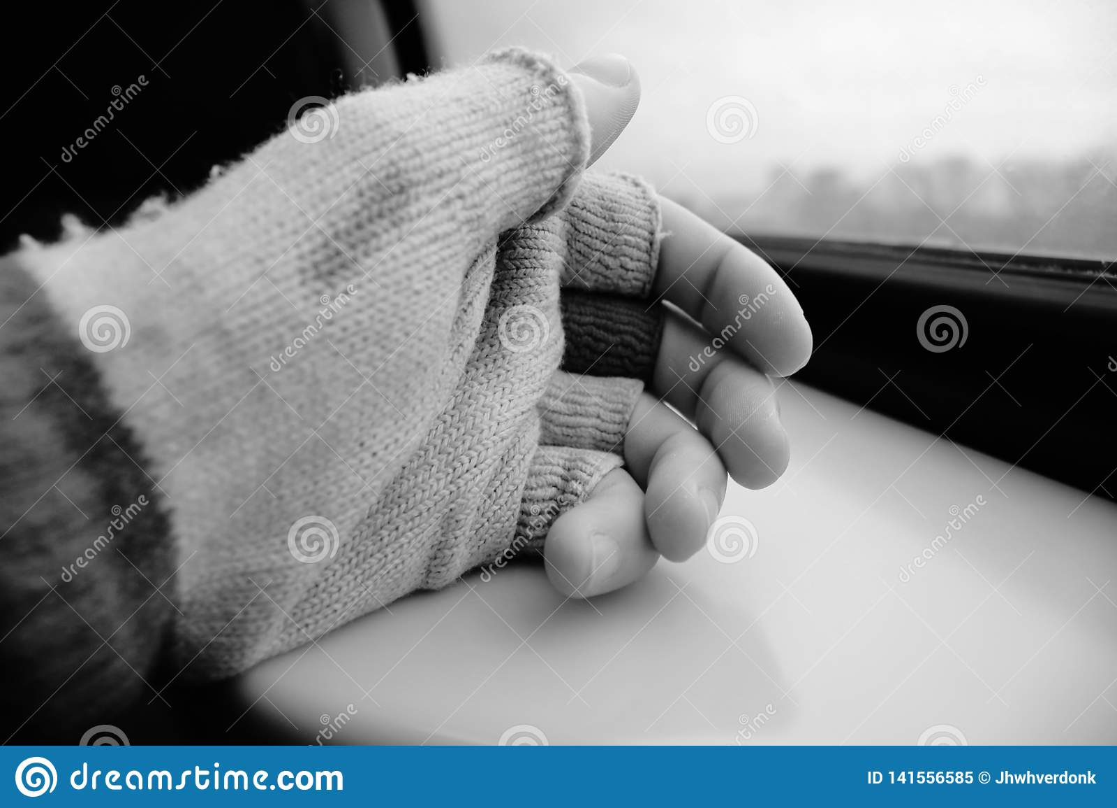 Mano con el guante viejo que tops del finger de la falta que descansan sobre una tabla con una visión afuera en blanco y negro