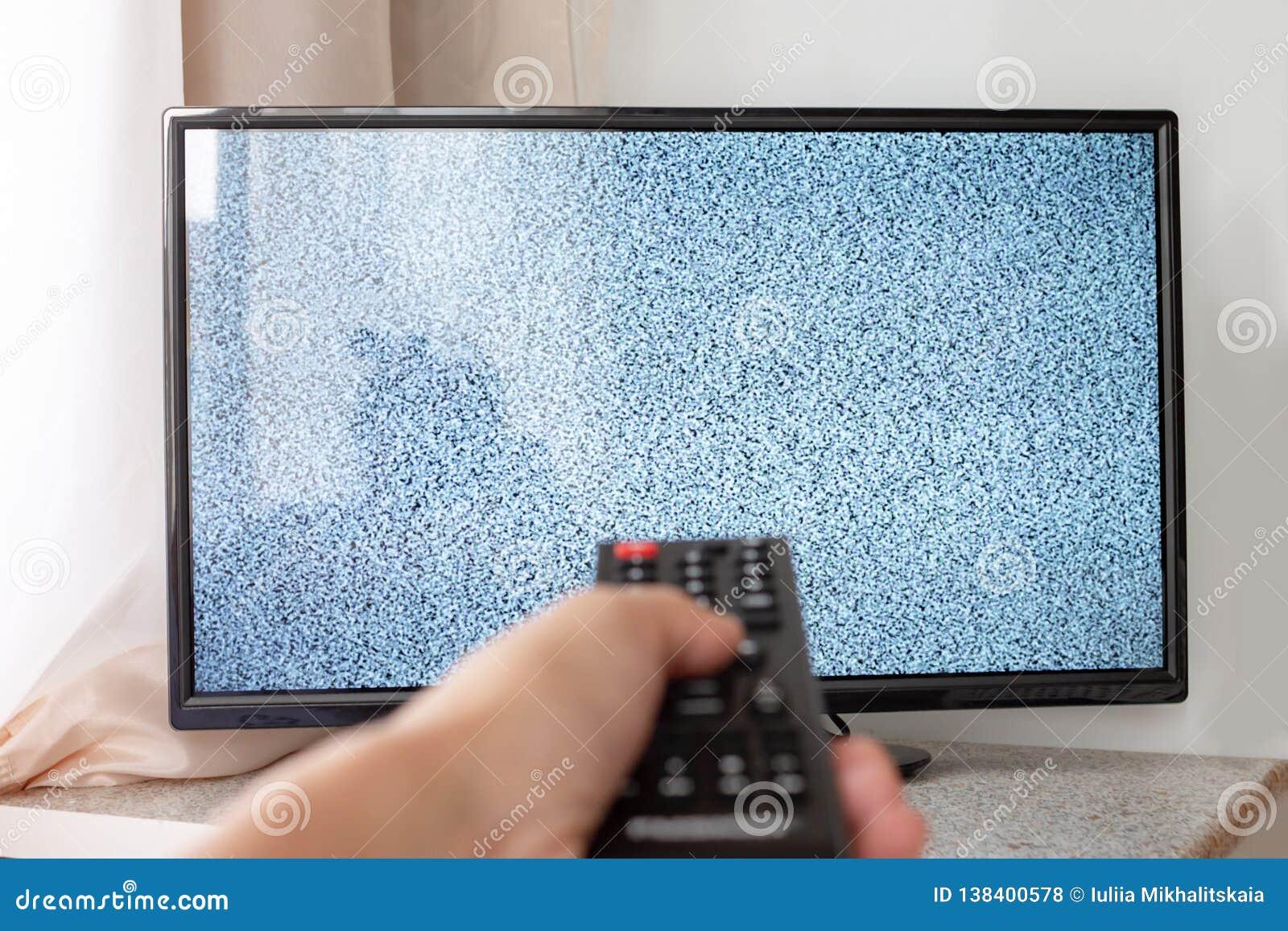 Mano con il telecomando della TV davanti allo schermo con rumore bianco su - sintonizzare i canali televisivi e collegare i probl