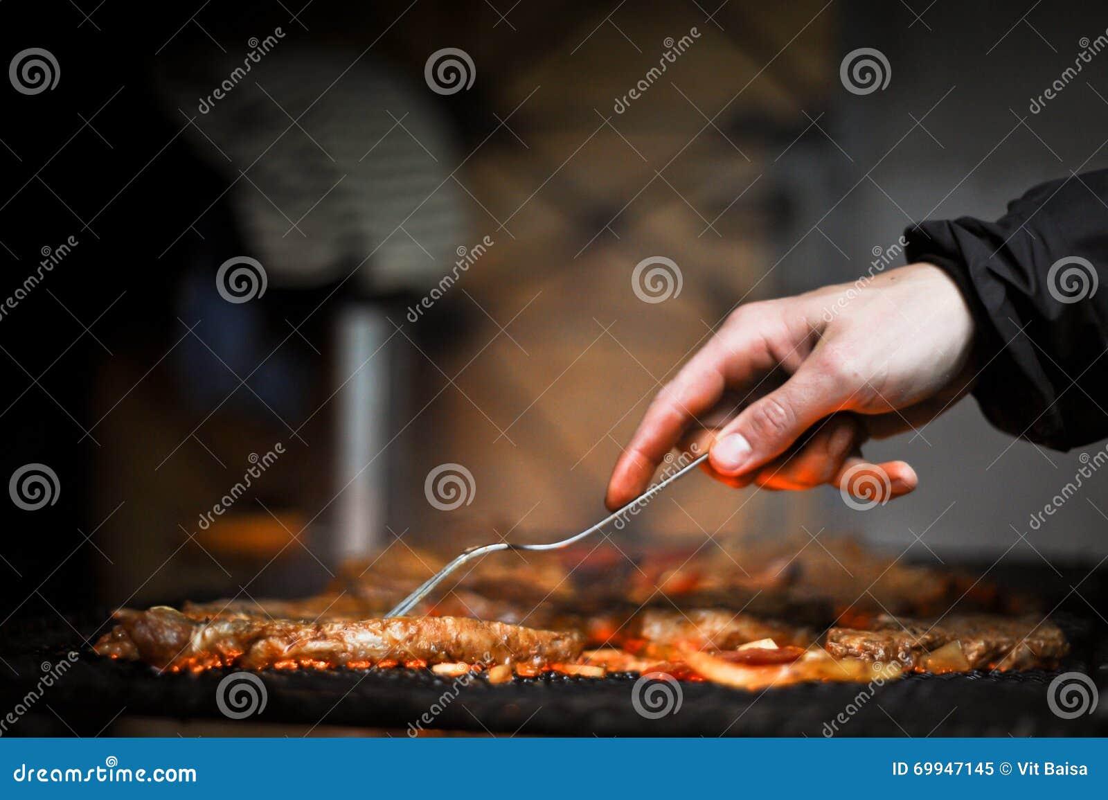 Mano con la bifurcación que da vuelta a la carne asada a la parrilla deliciosa con la verdura sobre los carbones en una parrilla