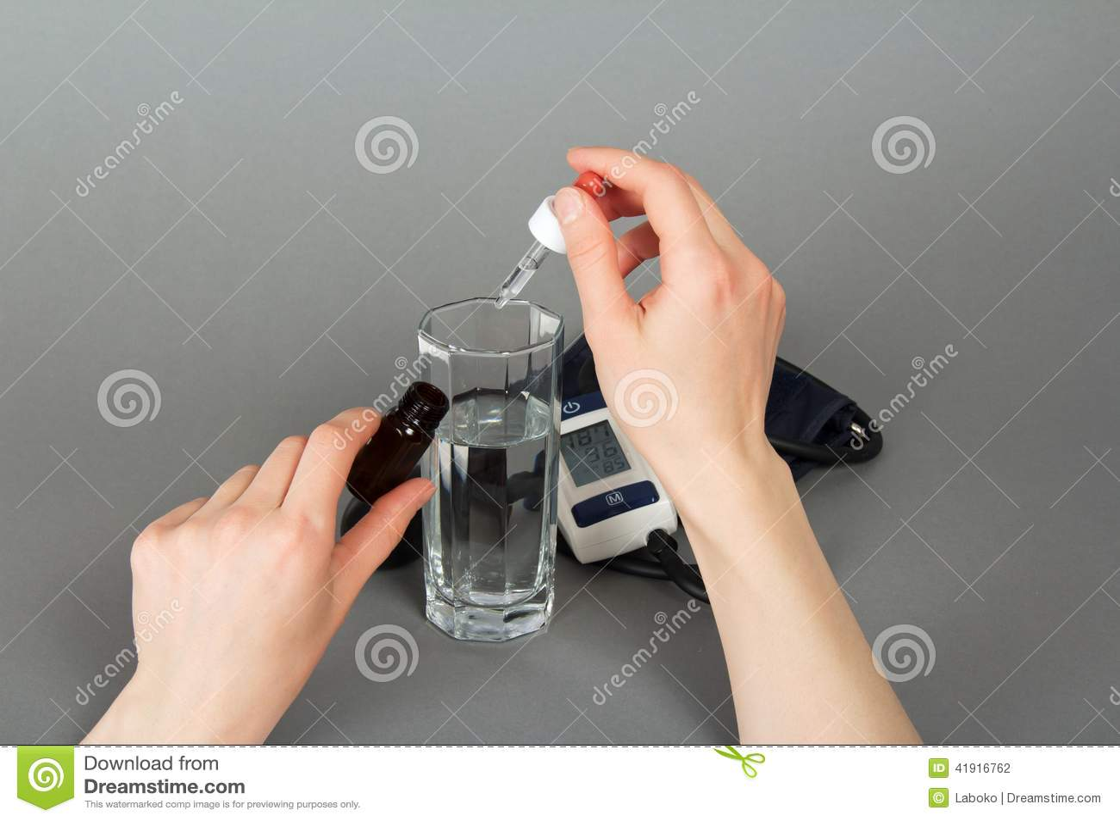 Mano con la medicina para la presión y un tonometer