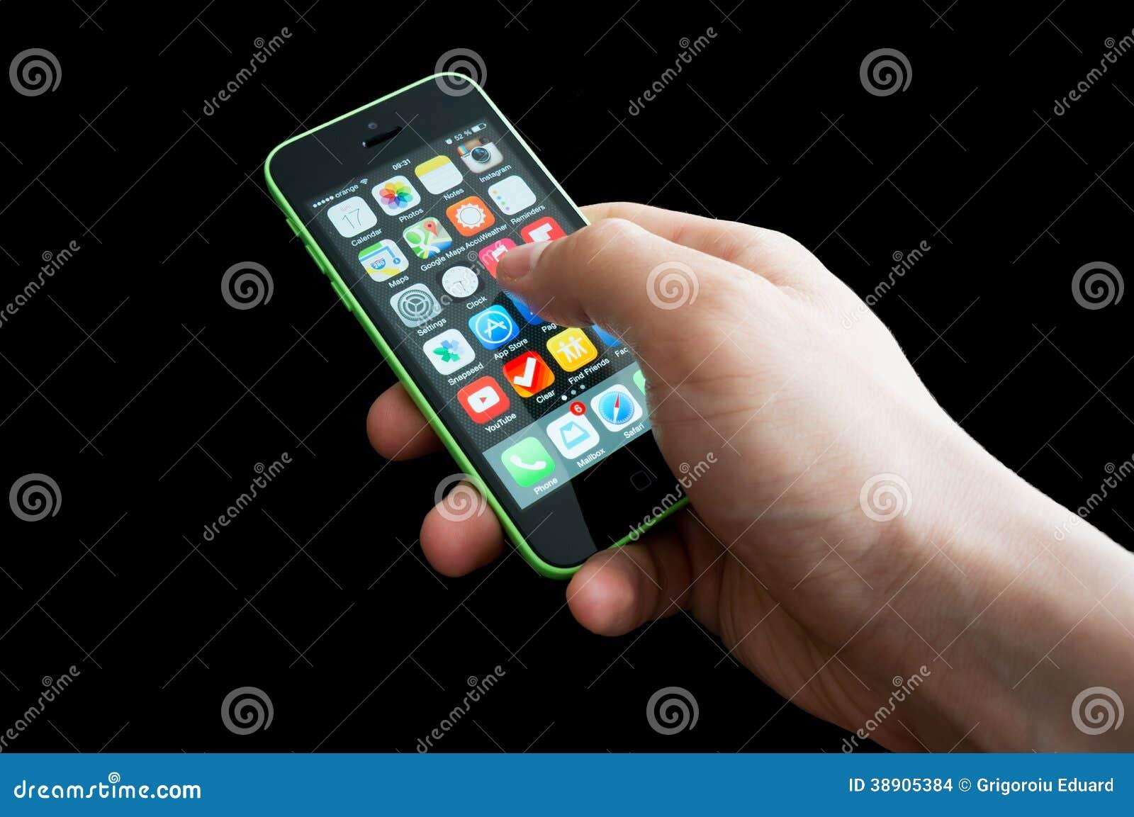 Mano con la pantalla de inicio de un iphone 5C