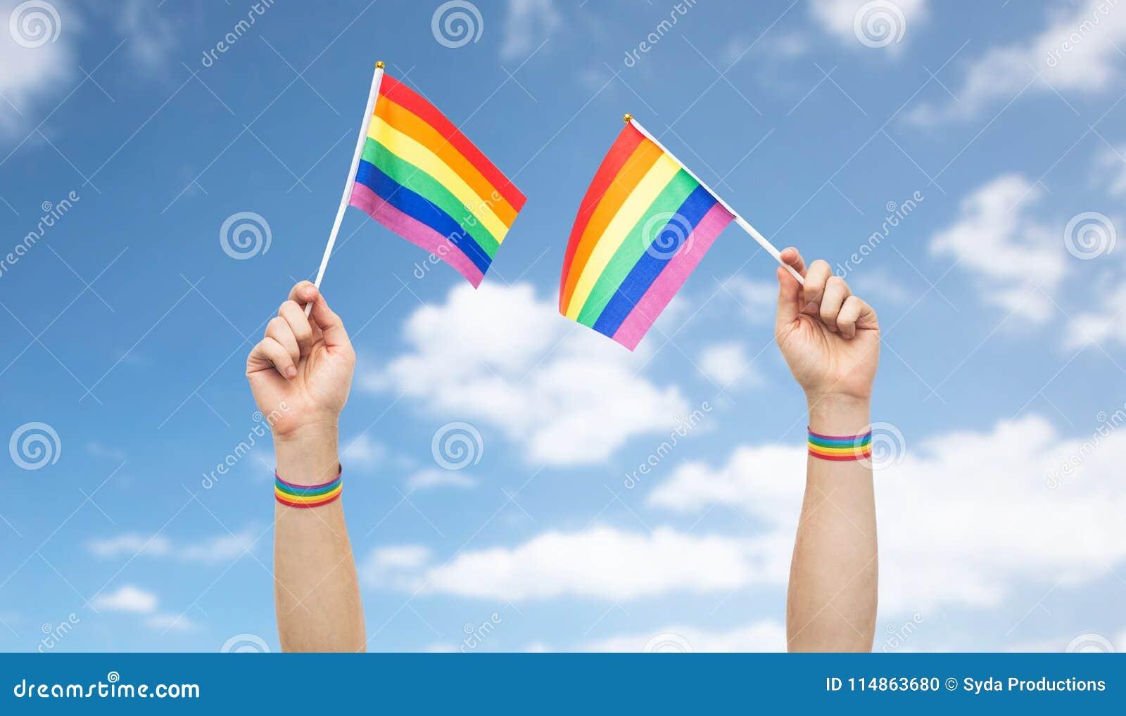 Mano con las banderas y las pulseras del arco iris del orgullo gay