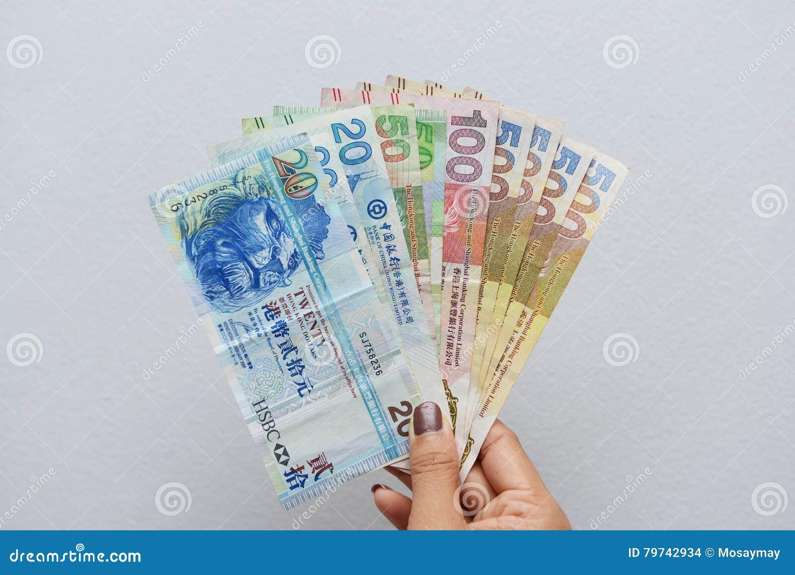 Mano con los billetes de dólar de Hong Kong
