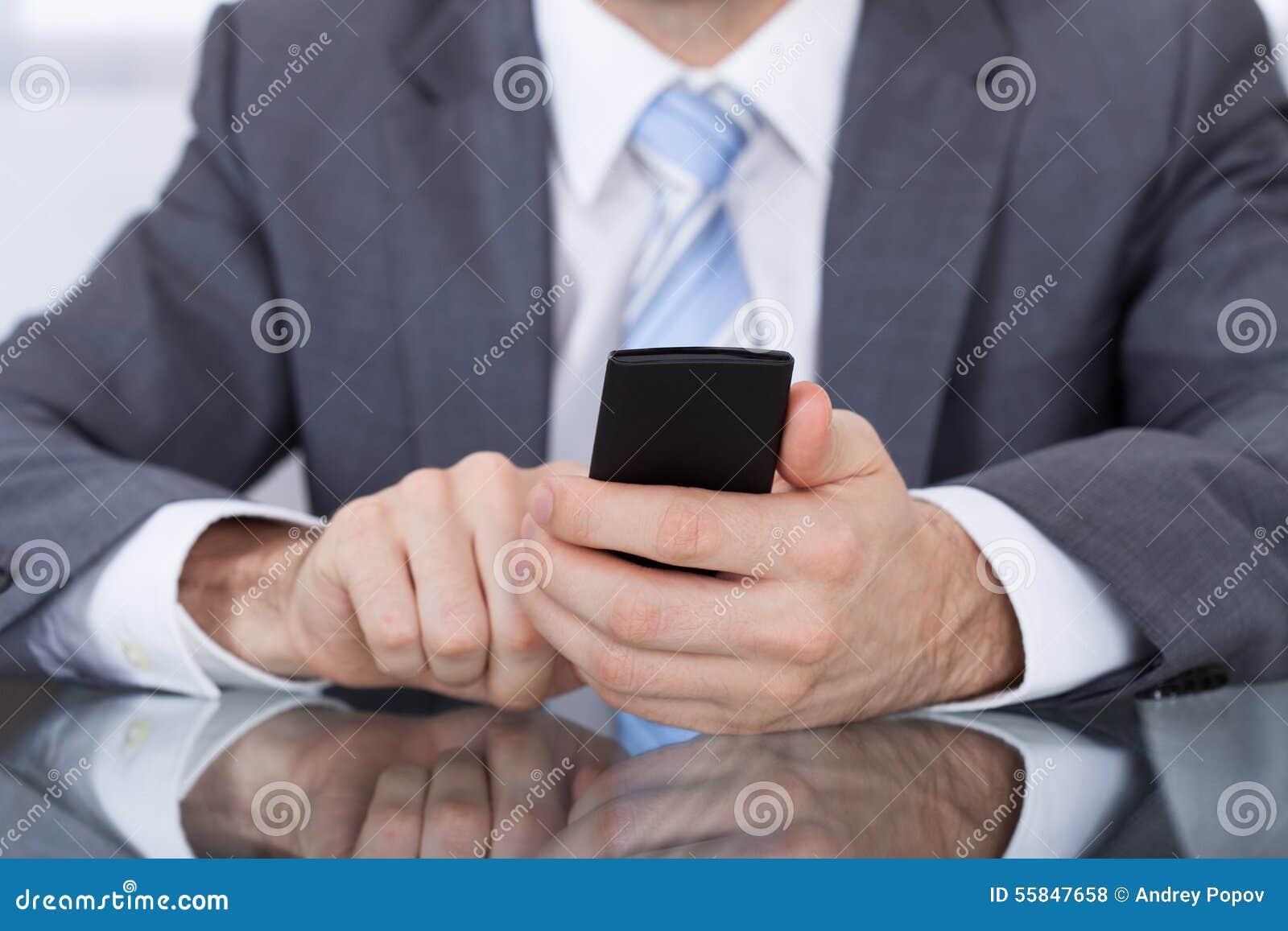 Mano de Holding Cellphone In del empresario
