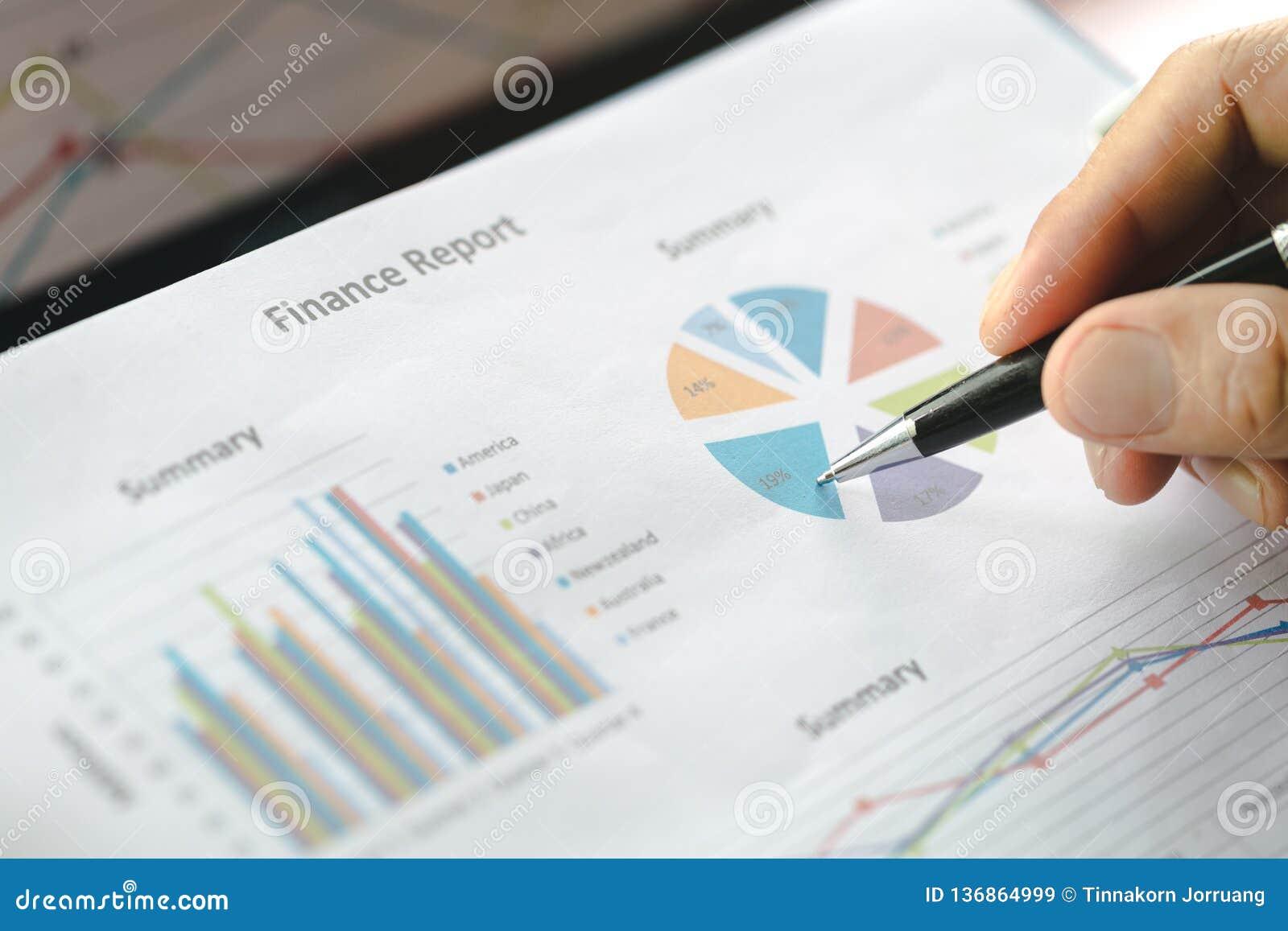 Mano de la escritura del hombre de negocios en el papel en la oficina, gráficos que muestran los resultados de su trabajo en equi