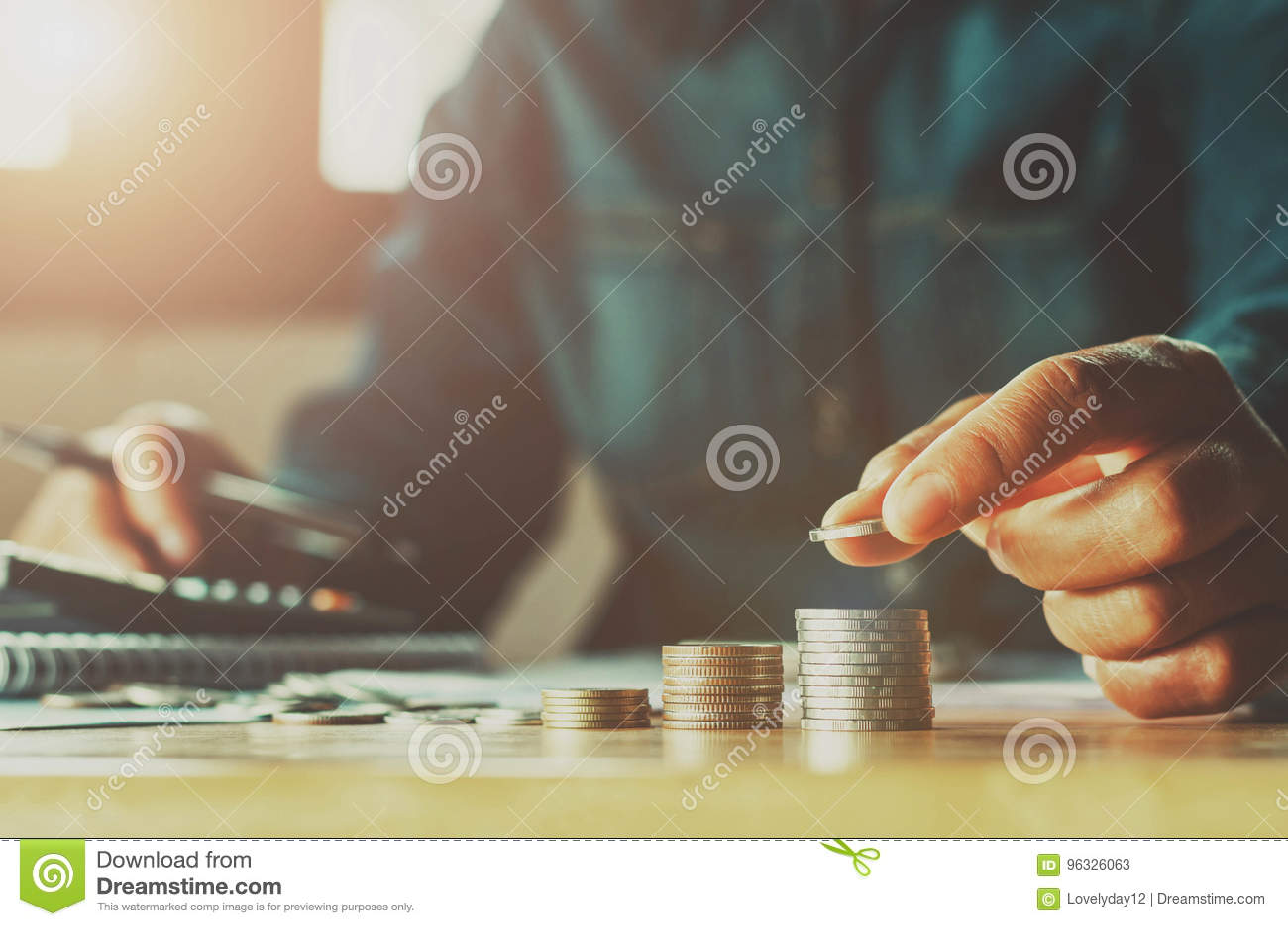 Mano de la mujer del dinero del ahorro que pone fina del negocio del concepto de la pila de la moneda