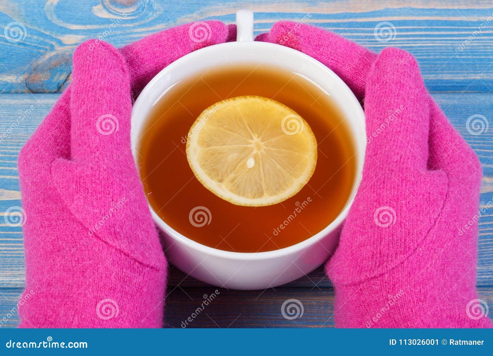 Mano de la mujer en los guantes que sostienen la taza de té caliente en la tabla