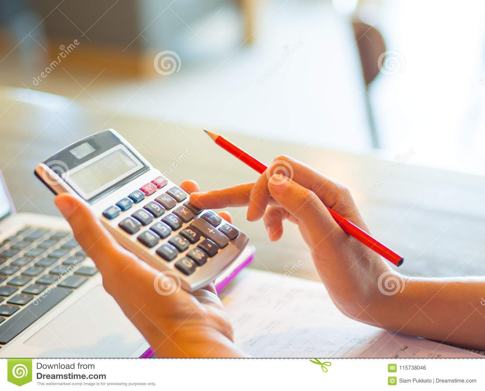 Mano de la mujer de negocios del primer usando una calculadora con el lápiz rojo en oficina del café