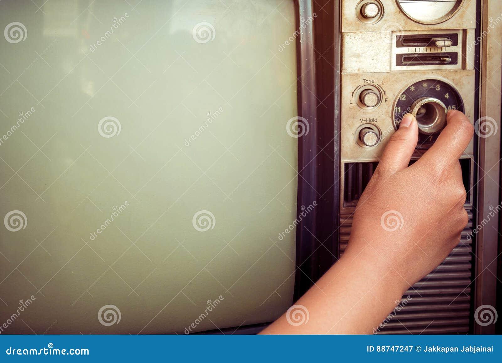 Mano de la mujer que ajusta la televisión del vintage con el botón del control