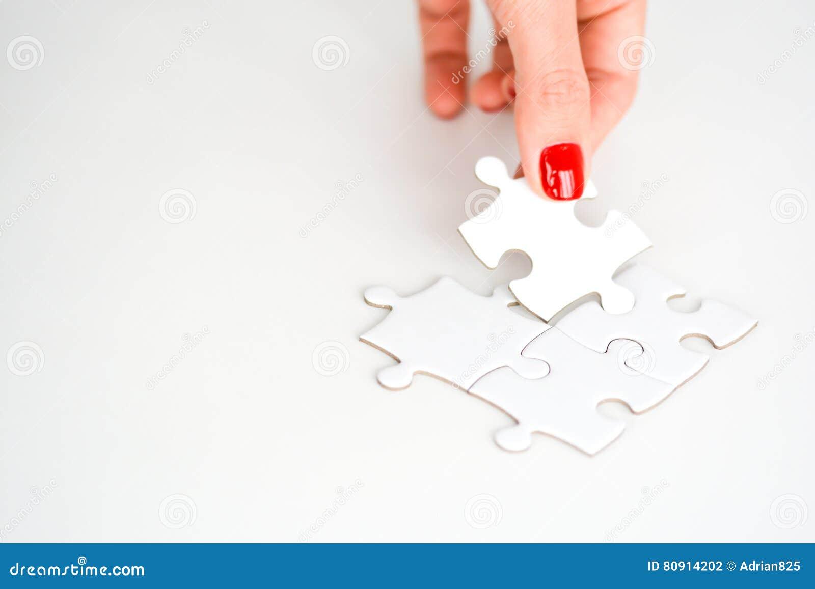 Mano de la mujer que cabe el pedazo correcto de rompecabezas que sugiere concepto del establecimiento de una red del negocio