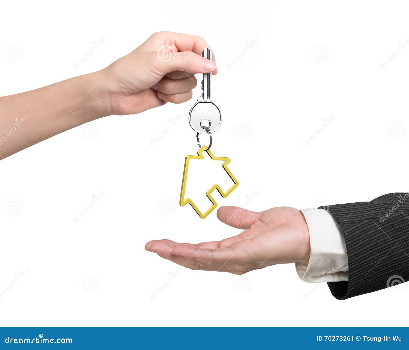 mano de la mujer que da llave con el llavero de la casa a