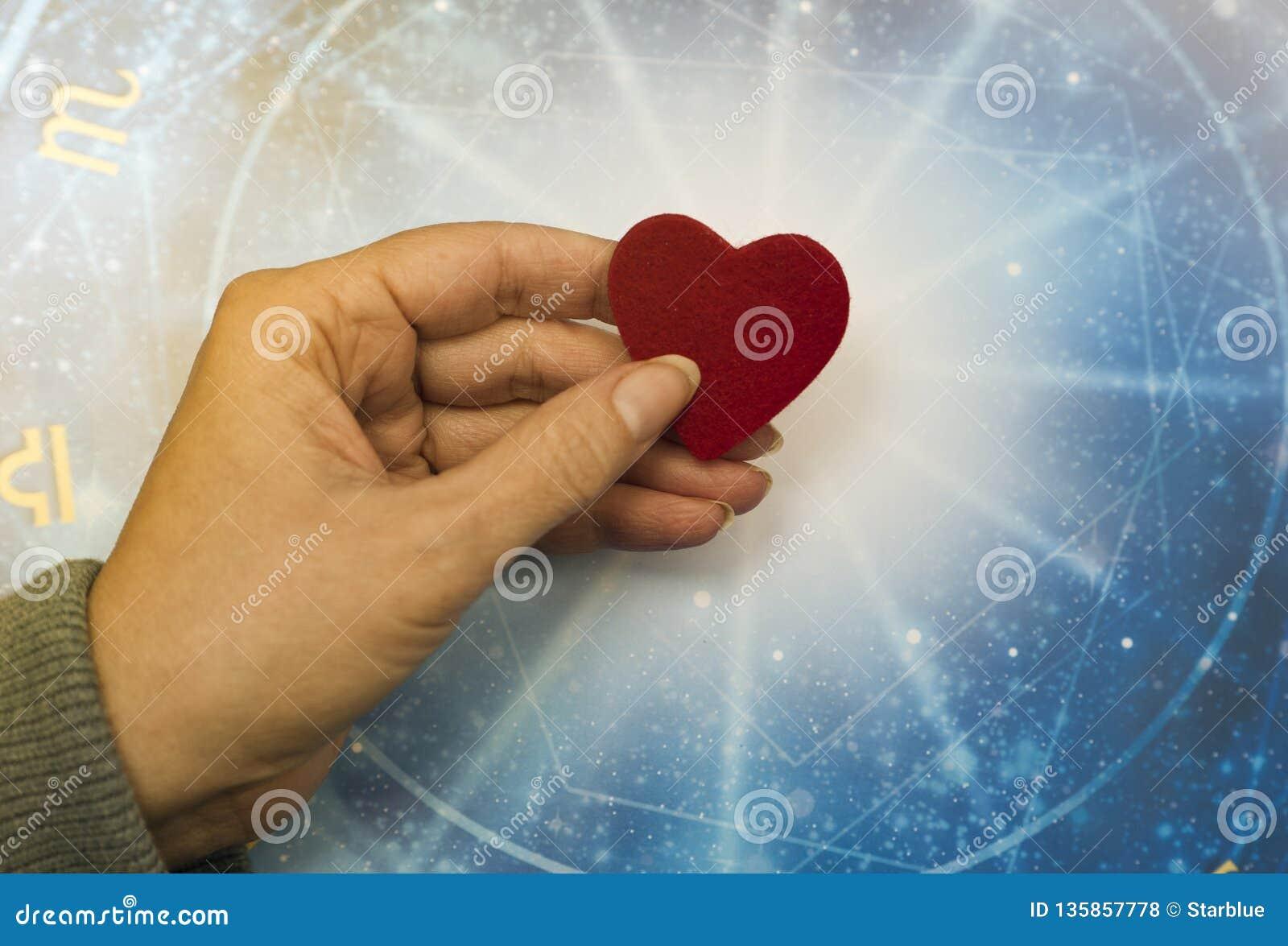 Mano de la mujer que guarda un corazón rojo sobre horóscopo azul como concepto de la astrología, del zodiaco y del amor