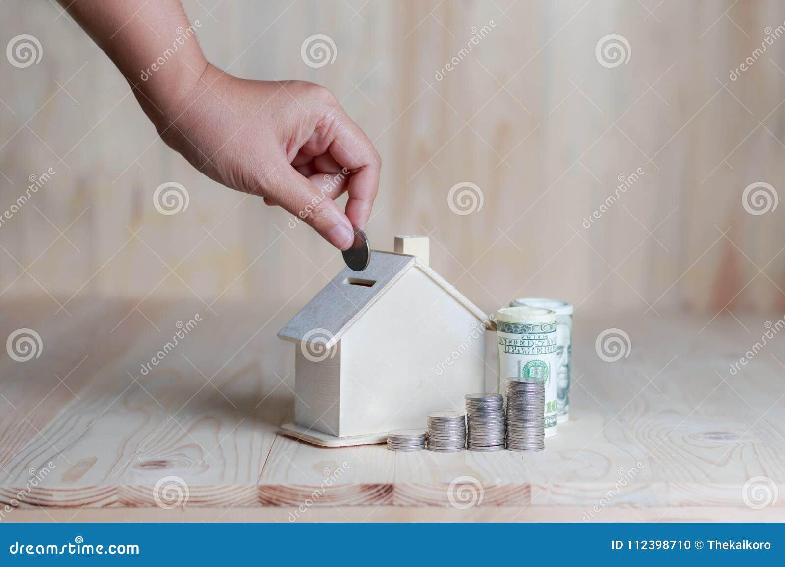 Mano de la mujer que introduce la moneda al financ de madera de la hucha de la casa
