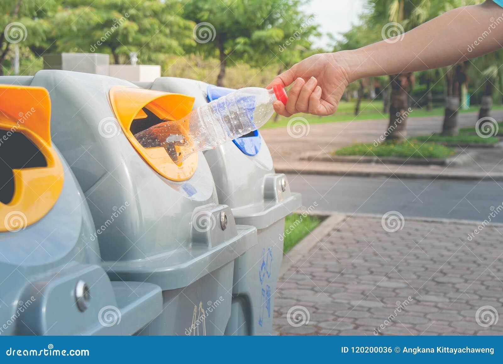 Mano de la mujer que pone la botella plástica usada en papeleras de reciclaje públicas o cubos de la basura segregados en parque