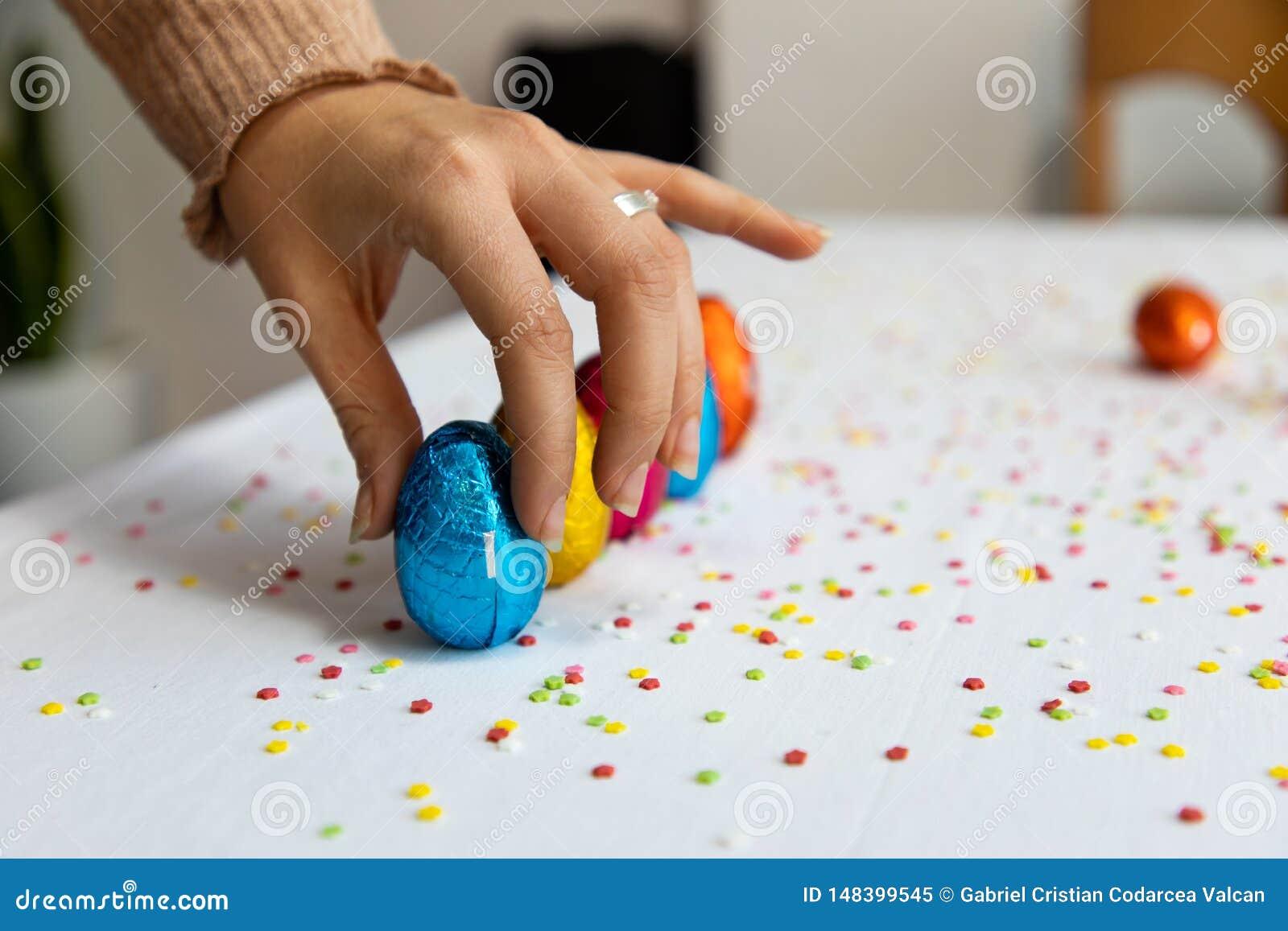 Mano de la mujer que pone los huevos de Pascua coloridos del chocolate