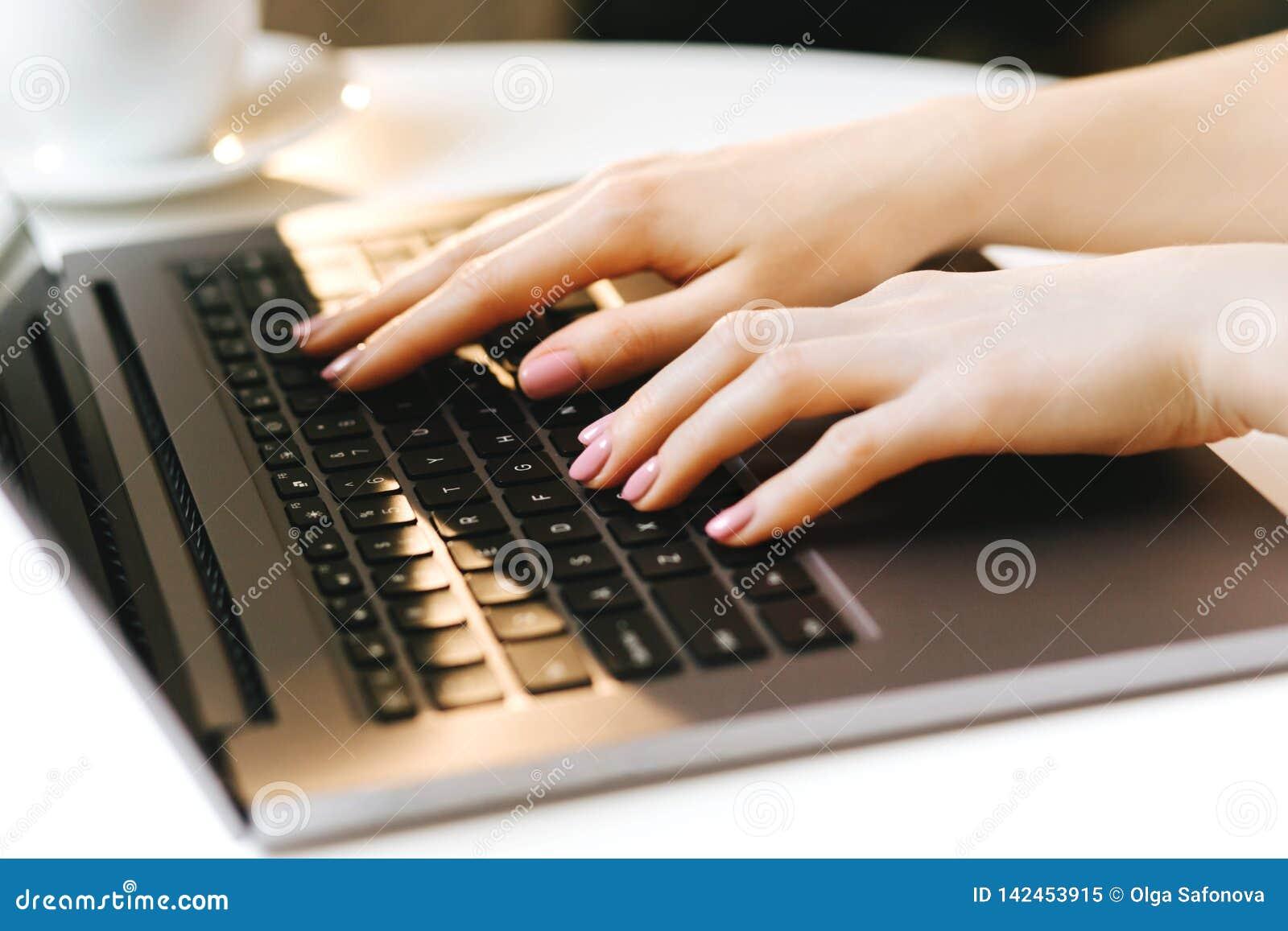 Mano de la mujer que pulsa en el teclado de la computadora portátil