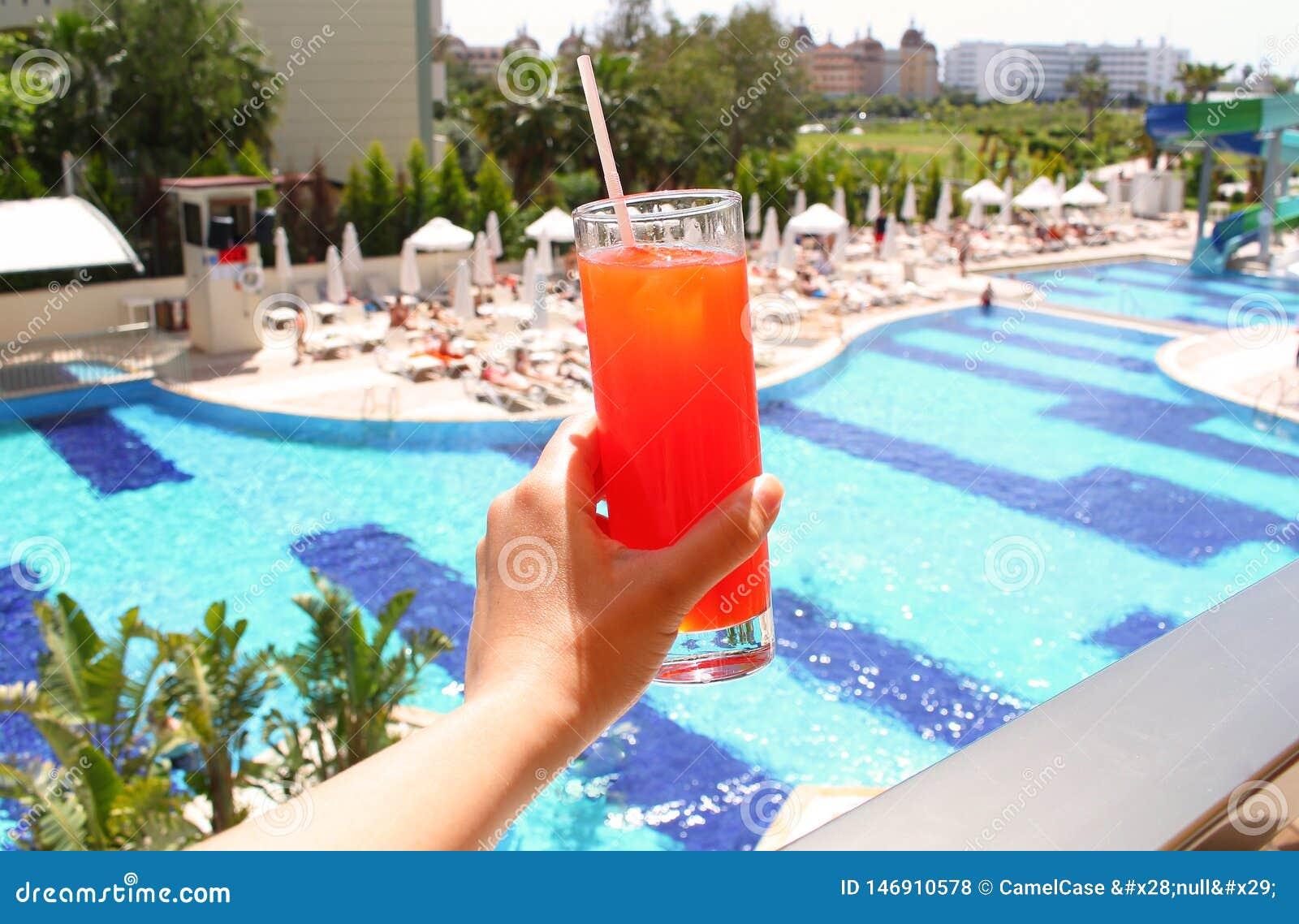 Mano de la mujer que sostiene el vidrio con un cóctel acodado en fondo de la piscina Viaje del verano, vacaciones, todo el concep