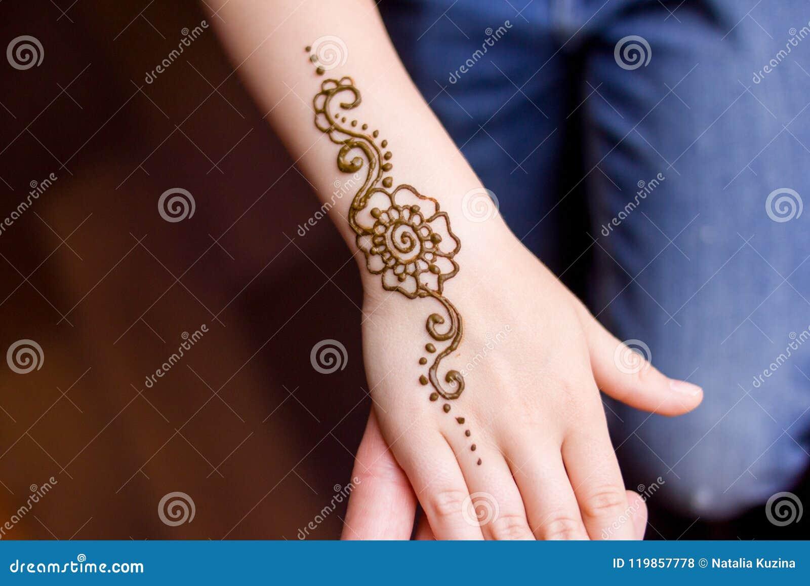 Mano de la pequeña muchacha que es adornada con el tatuaje del mehendi de la alheña Primer, visión de arriba - concepto de la bel
