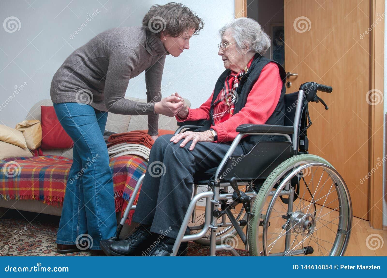 Mano de la tenencia de la mujer joven de la mujer mayor triste con la silla de ruedas