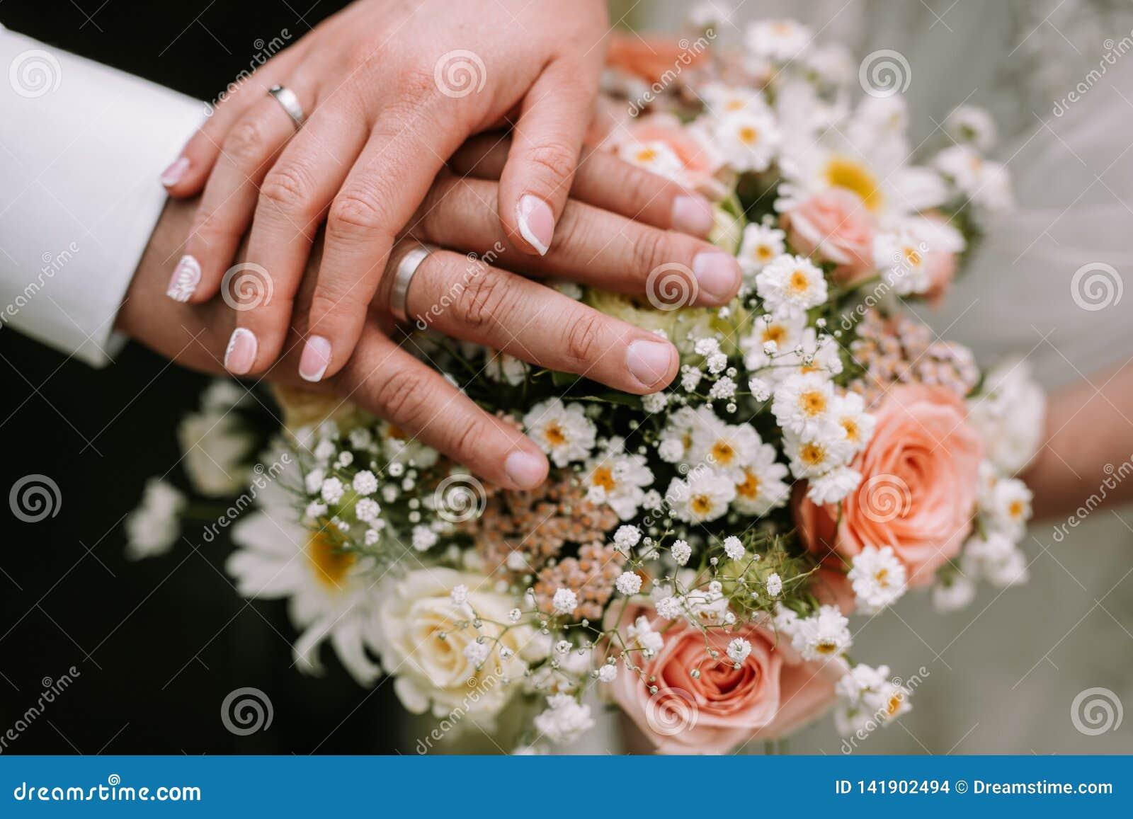 Mano de la tenencia de novia y del novio en el ramo