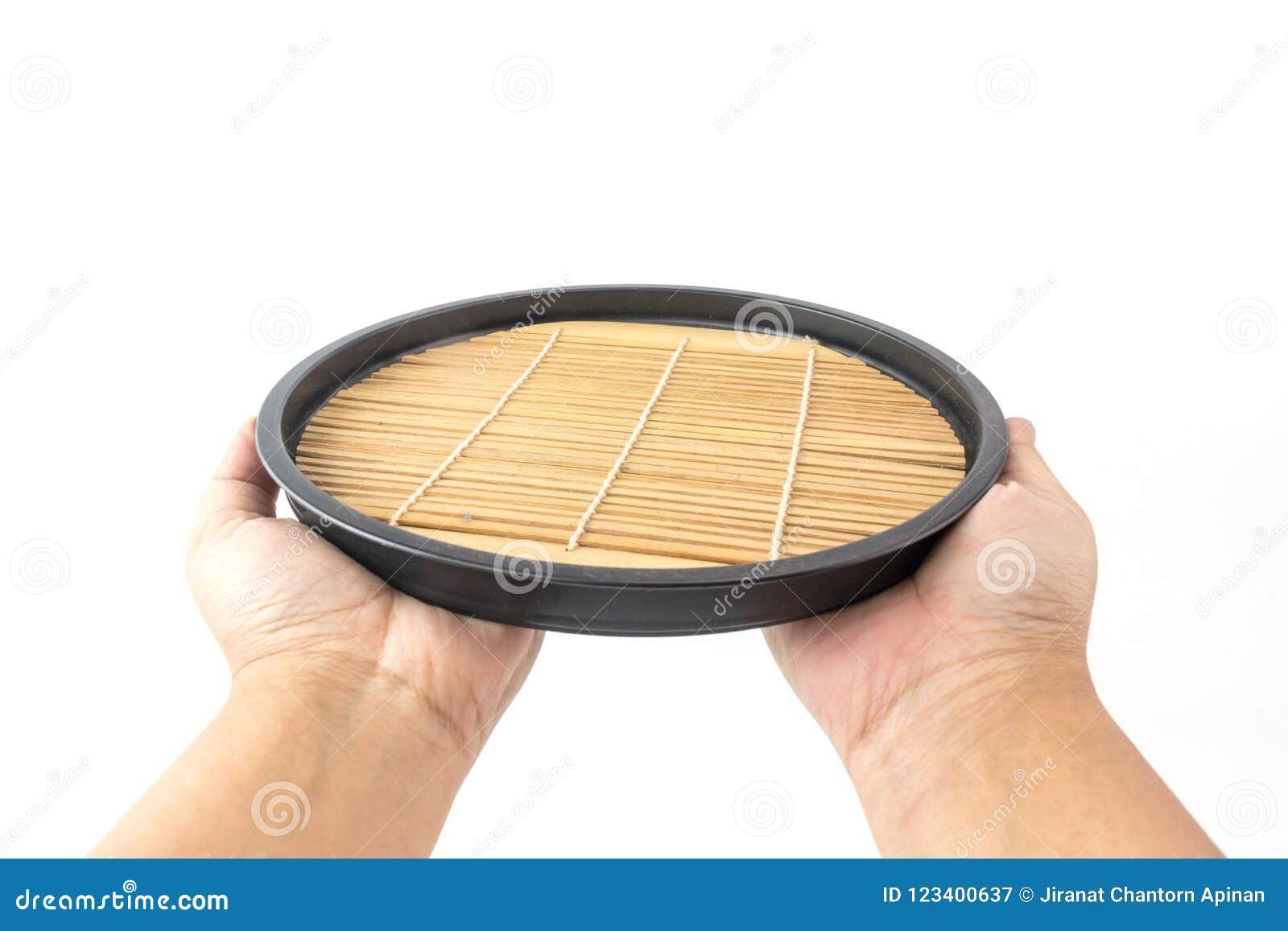 Mano de un hombre que sostiene una bandeja de madera espiral japonesa con el bambú