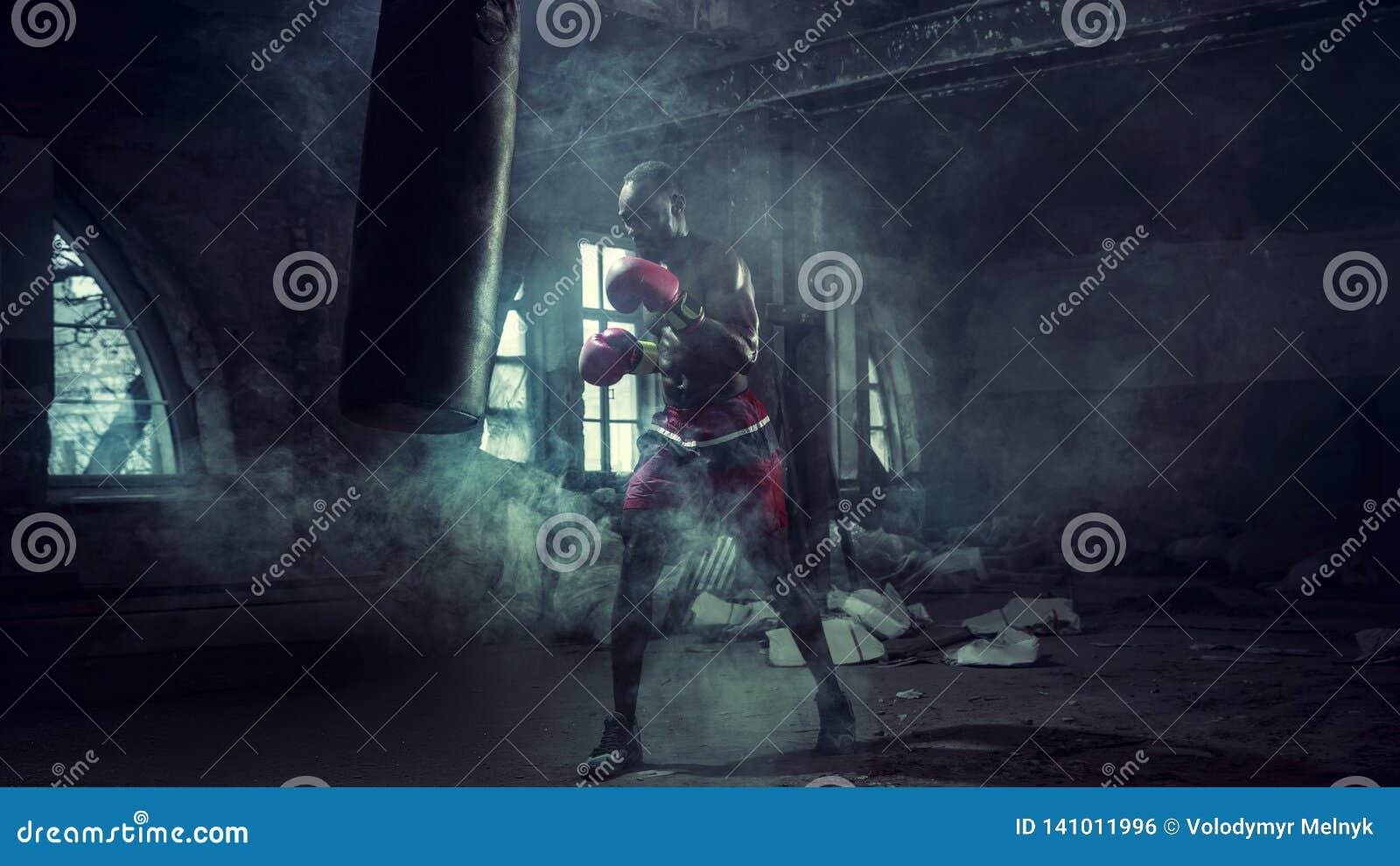 Mano del boxeador sobre fondo negro Concepto de la fuerza, del ataque y del movimiento